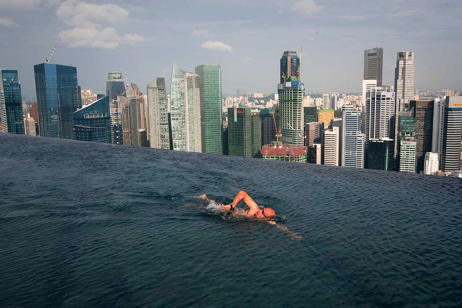 A guest swims in the infinity pool of the Skypark that tops the Marina Bay Sands hotel towers in Singapore June 24, 2010