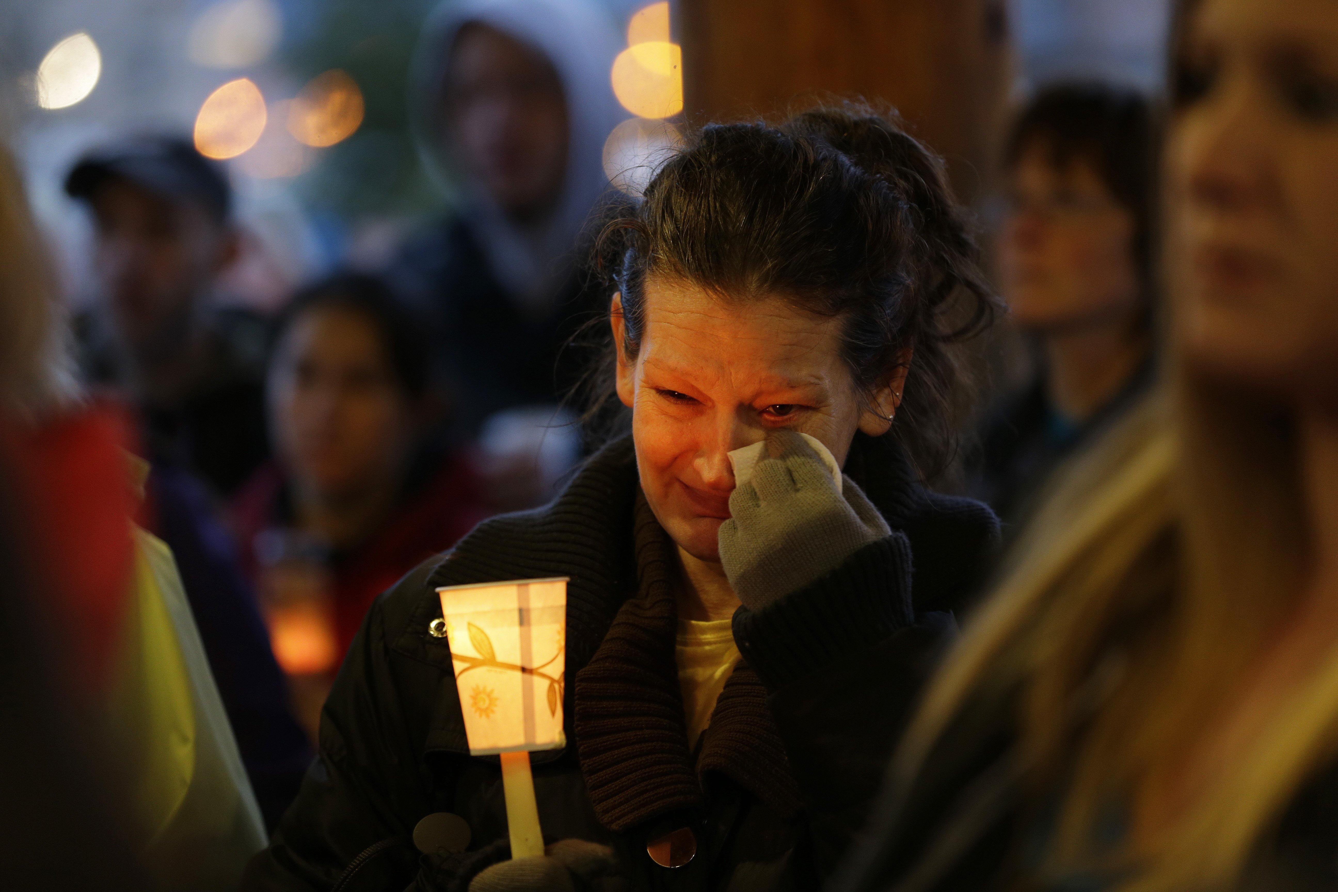 Teresa Welter cries as she holds a candle at a candlelight vigil for the victims of the deadly mudslide in Arlington, Wash., March 25, 2014.