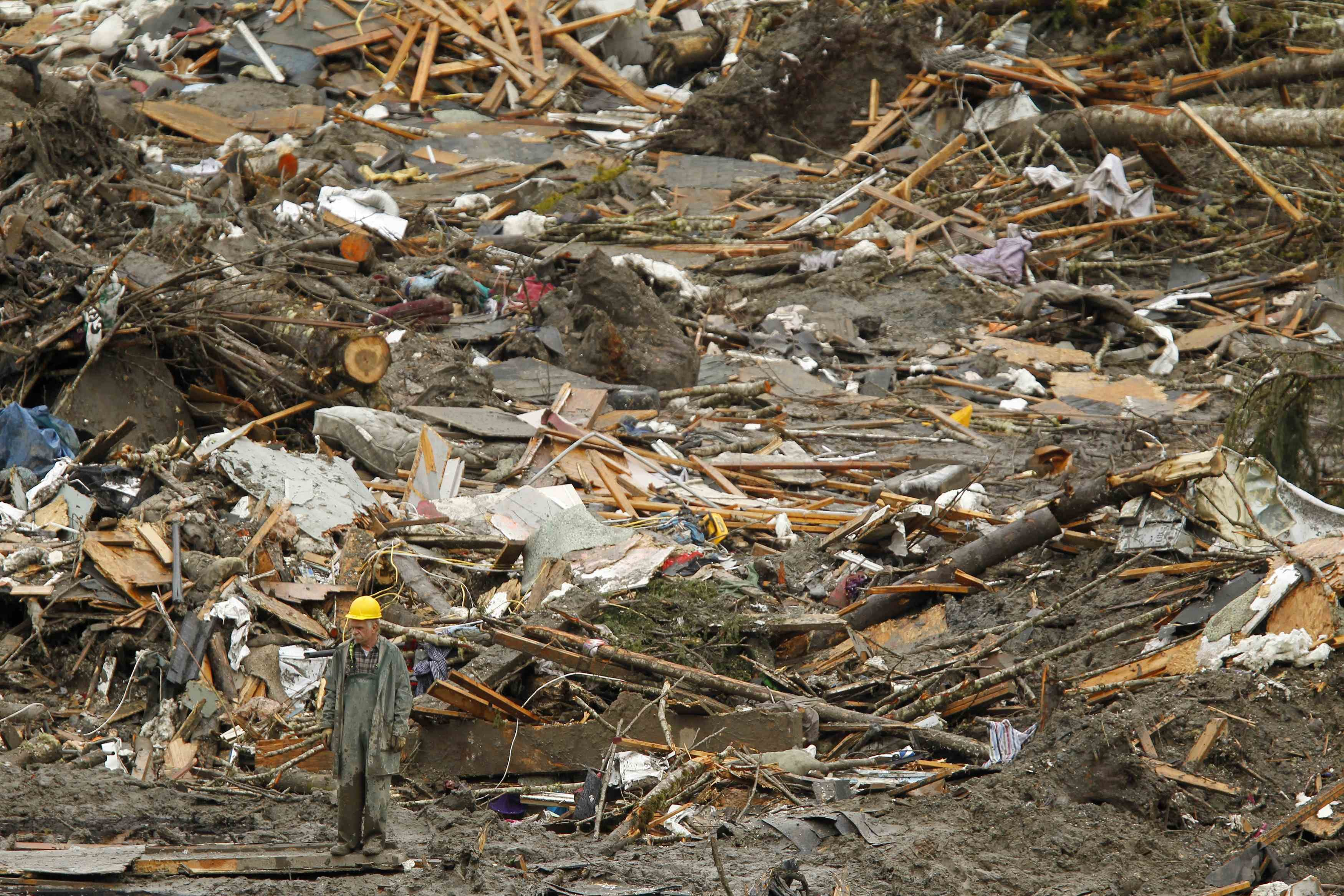 A rescue worker looks over the debris pile from the mudslide in Oso, Wash., March 27, 2014.
