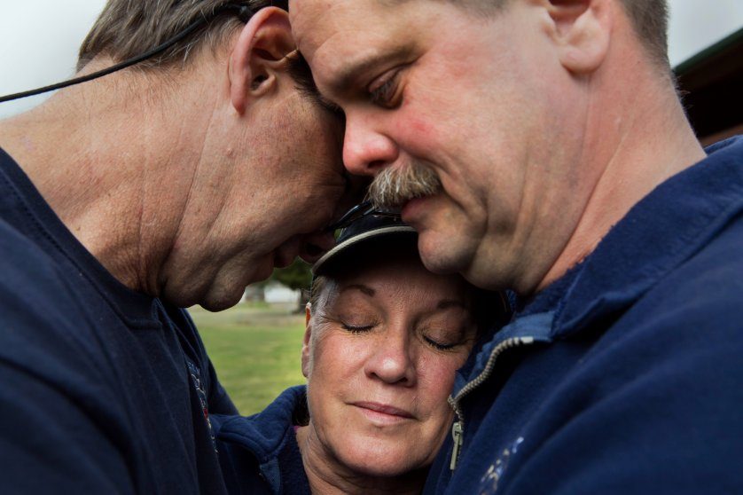 Darrington Fire District 24 volunteer firefighters, Jeff McClelland, left, Jan McClelland, center, and Eric Finzimer embrace each other, March 26, 2014, in Darrington, Wash., after saying a prayer for the victims and survivors of the massive mudslide.
