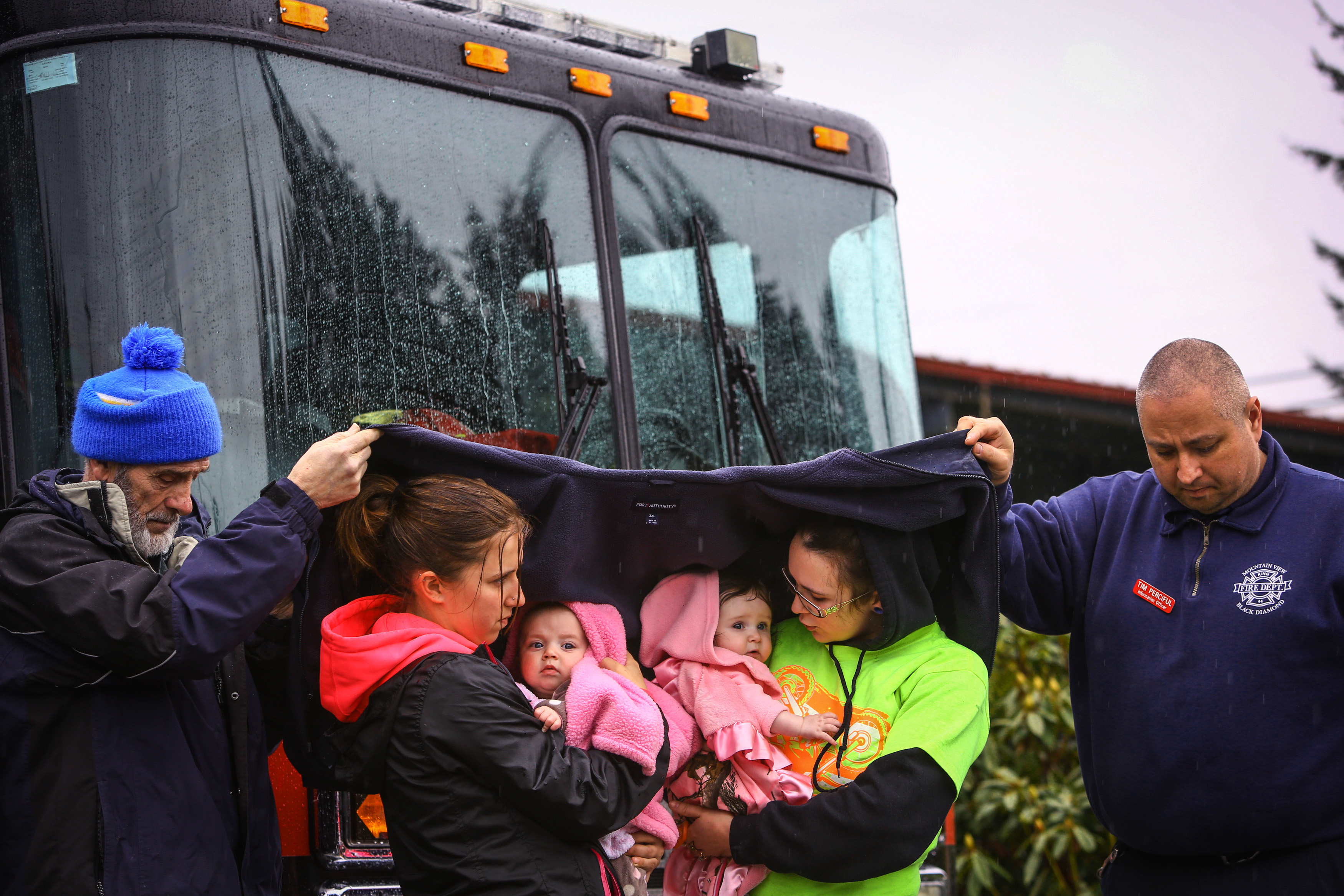 Volunteer Ralph Jones, left, and Tim Perciful of the Mountainview, Black Diamond Fire Department, help keep Klarissa Calviste and her daughter Kielie Braaten, left, and Brooke Odenius and her daughter Bexli dry as they observe a state-wide moment of silence for victims of the Oso mudslide at the Darrington Fire Dept., March 29, 2014.