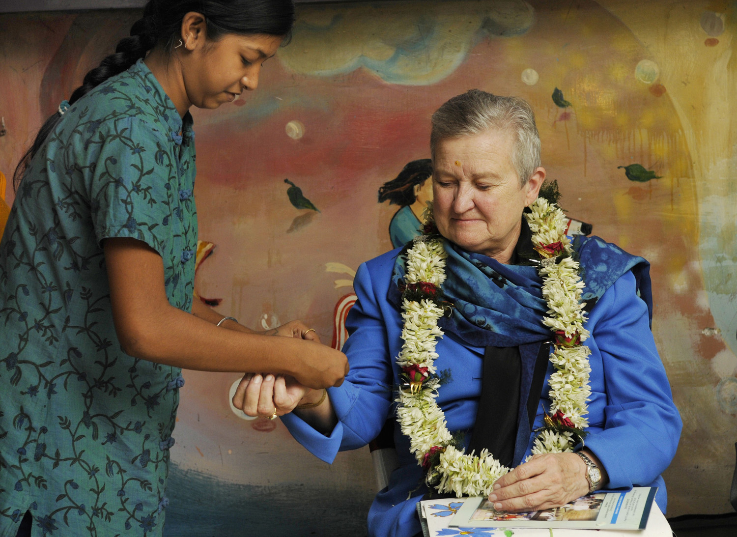 A girl ties a band to the wrist of U.S. ambassador to India, Nancy Powell, during her visit to NGO Child In Need Institute on May 21, 2013 in Kolkata, India.