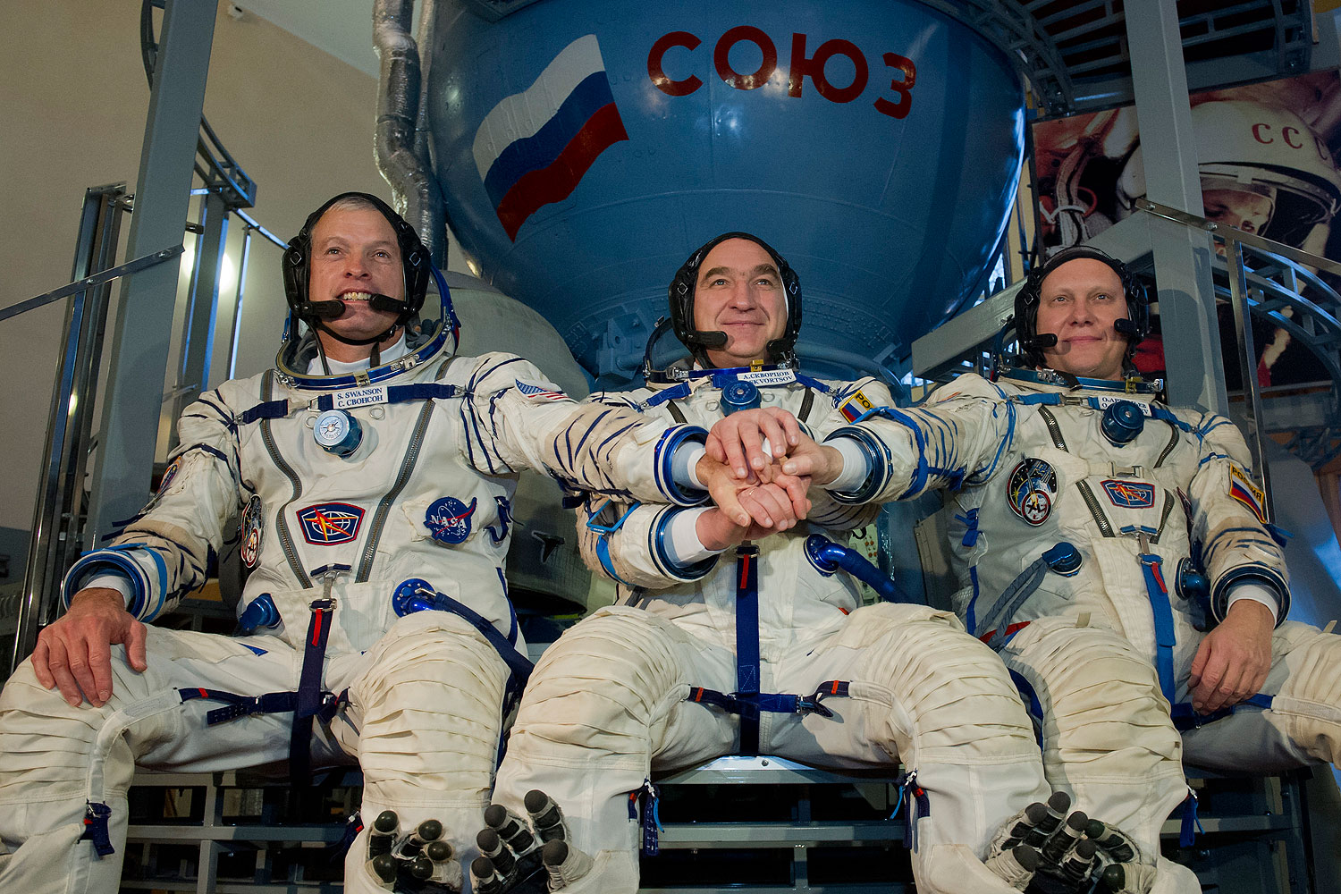 U.S. NASA astronaut Steven Swanson (L) joins hands with Russian cosmonauts, Alexander Skvortsov (C) and Oleg Artemyev (R), in front of a mock-up of a Soyuz TMA spacecraft at the Gagarin Cosmonauts' Training Centre in Star City centre outside Moscow, on March 5, 2014