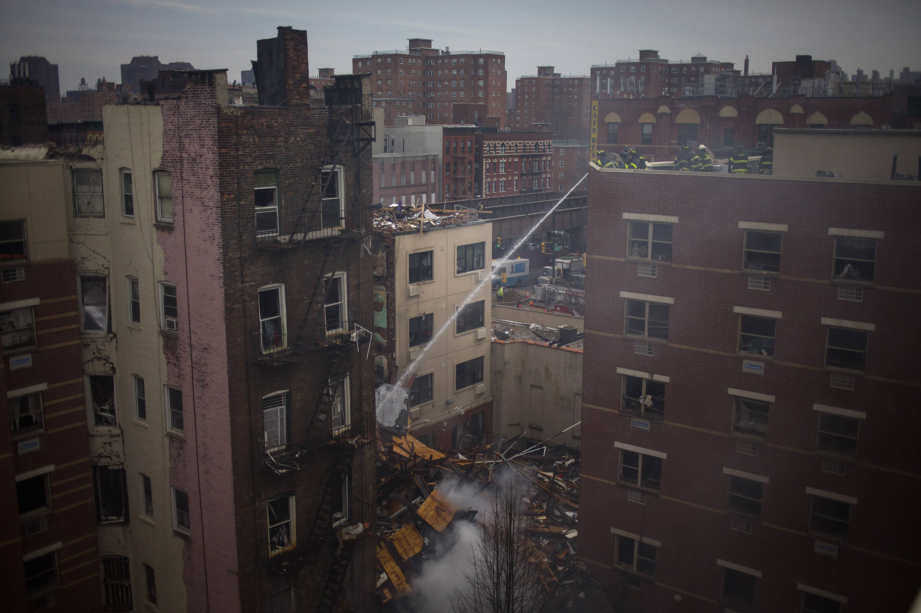New York City firefighters examine the rubble at an apparent building explosion fire and collapse in Harlem.