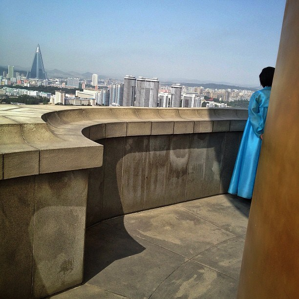 A North Korean tour guide stands on the top of Juche Tower in Pyongyang and looks across the Taedong River at the city below, September 17, 2013.