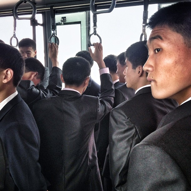 North Korean men on an airport transport bus headed to the Air Koryo flight for Beijing, Pyongyang Sunan International Airport, September 24, 2013.