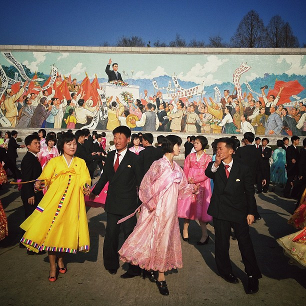 North Koreans dance a traditional folk dance together beneath a huge mosaic of the late leader Kim Il Sung in Pyongyang, April 11, 2013.