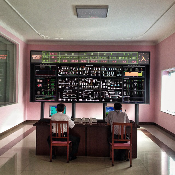 Men sat working beneath a control board at a Pyongyang factory, October 16, 2013.