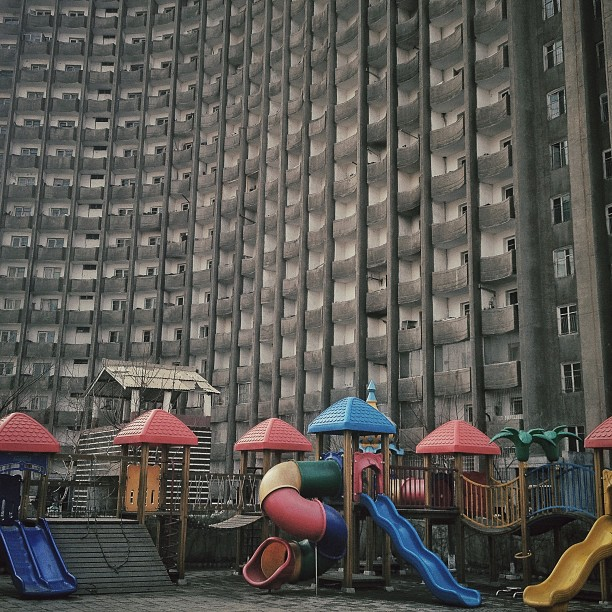 An apartment block stands above the schoolyard playground equipment of a Pyongyang kindergarten, March 12, 2013.