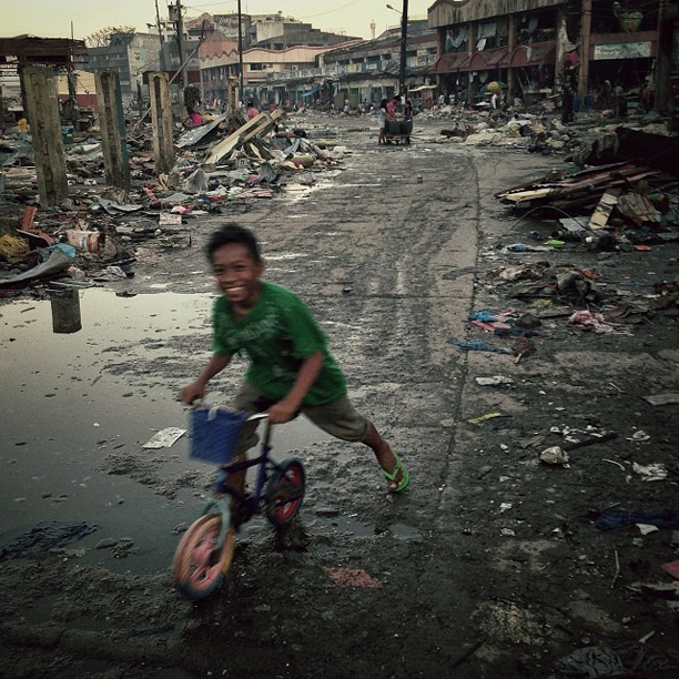 A boy plays in the street in the Typhoon Haiyan destroyed town of Tacloban, Philippines, November 17, 2013.