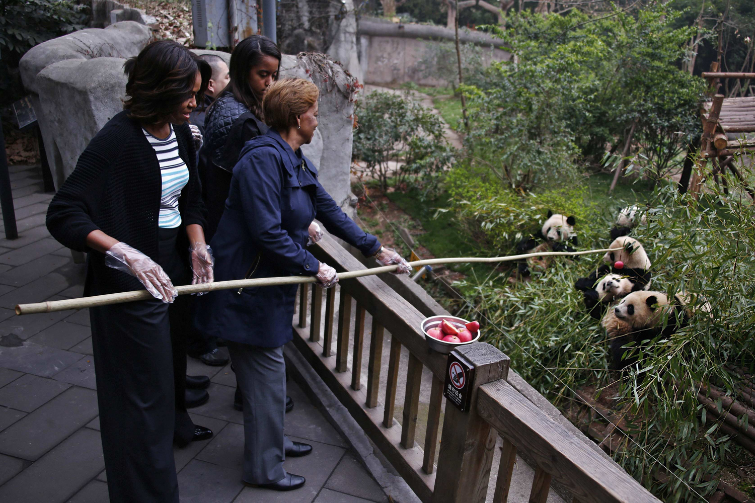 Mar. 26, 2014. U.S. first lady Michelle Obama (L) and her mother Marian Robinson (R) feed apples to giant pandas as Malia looks on during their visit at Giant Panda Research Base in Chengdu, Sichuan province.
