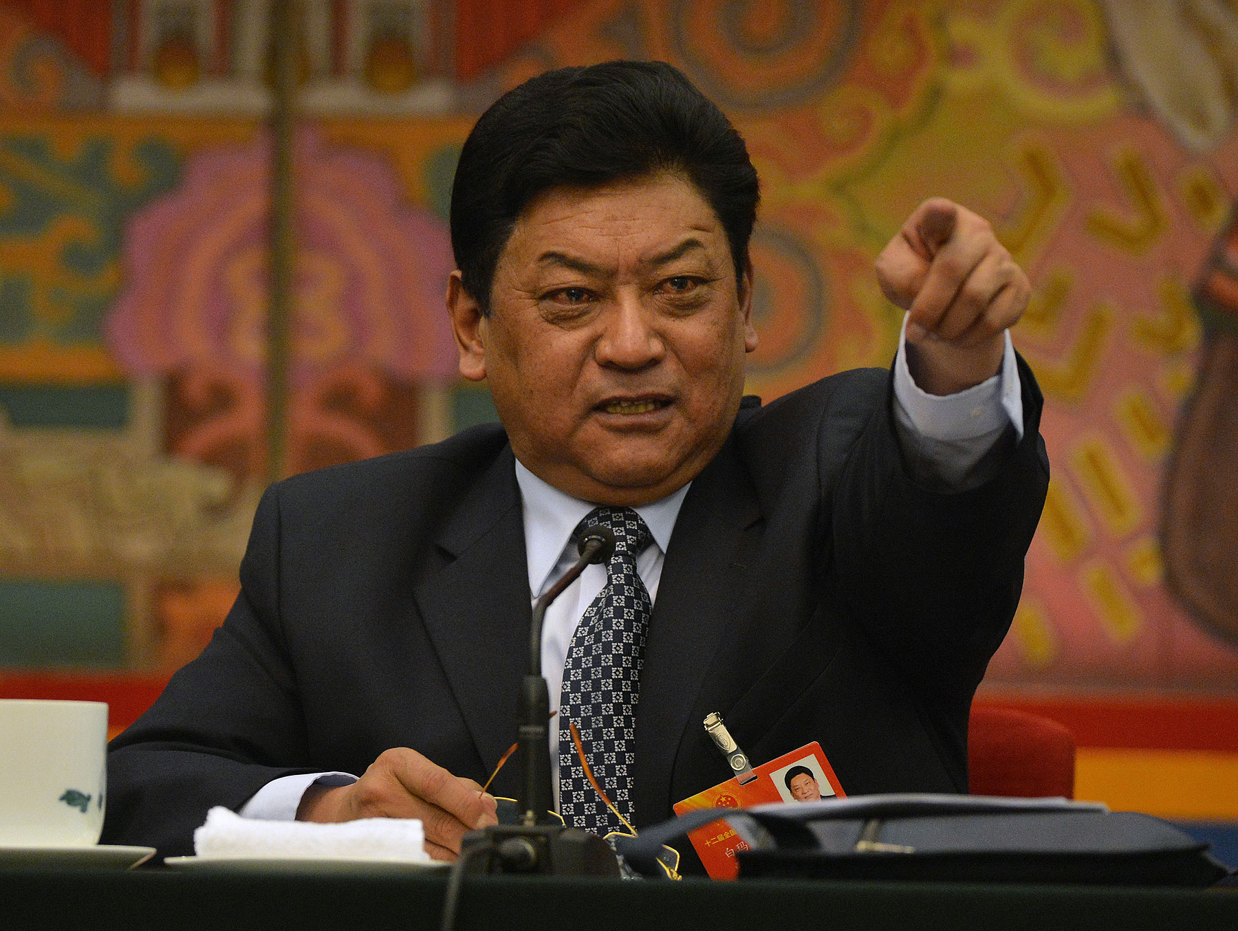 Padma Choling, head of China's Tibet Autonomous Region Congress gestures during their open session in the Great Hall of the people at the National People's Congress in Beijing on March 8, 2013