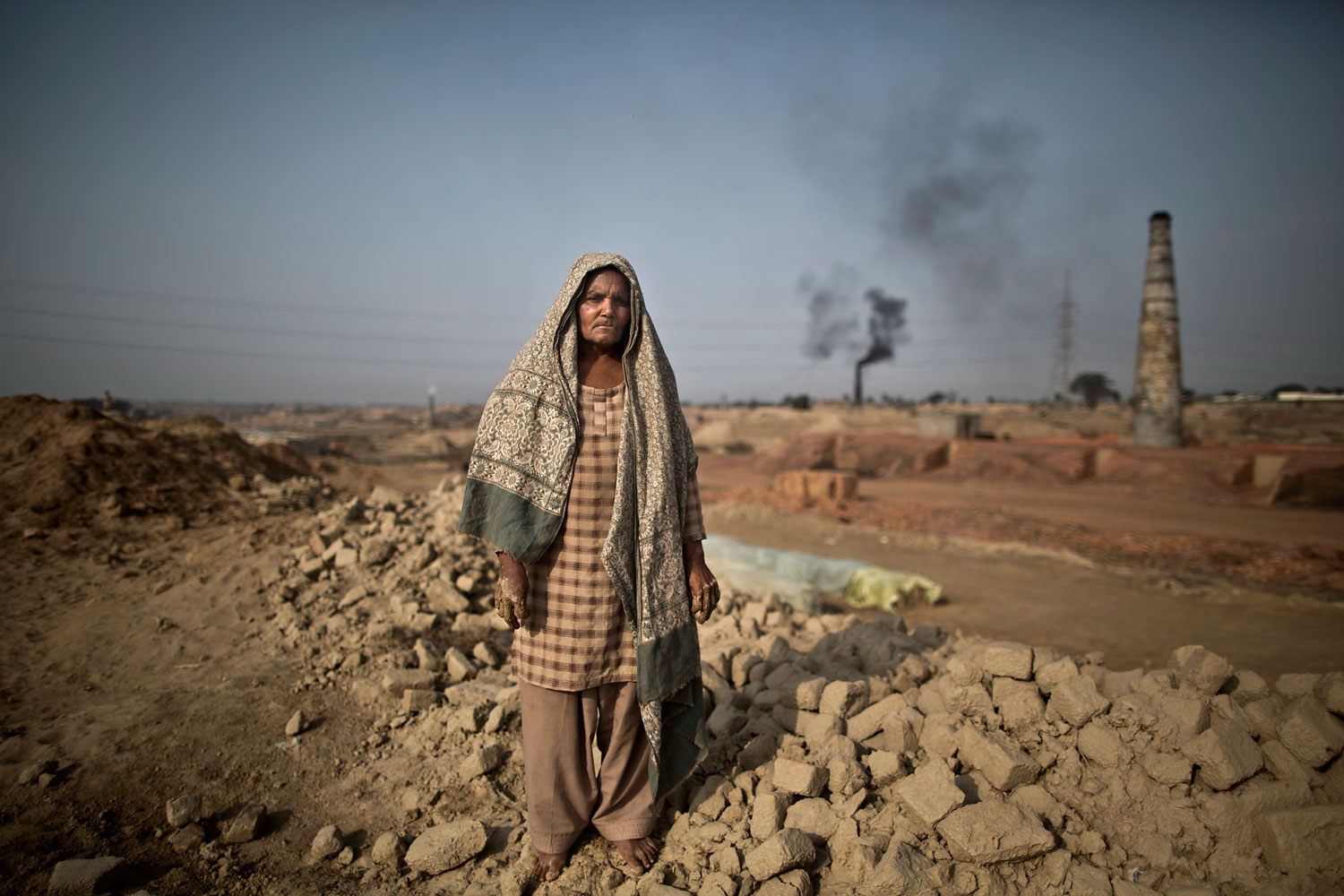 Emna Mohammed, 65, a Pakistani brick factory worker, poses for a picture at the site of her work in Mandra, near Rawalpindi, Pakistan, March 5, 2014. Emna inherited her late husband's debt to the employer the amount of 95,000 rupees (approximately $950).