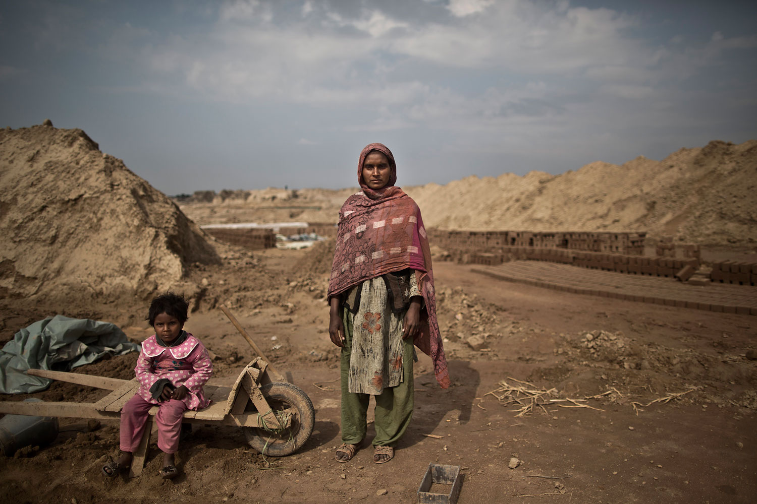 Sofia Zahour, 25, a Pakistani brick factory worker, poses for a picture as standing next to her daughter Alina, 2, at the site of her work in Mandra, near Rawalpindi, Pakistan, March 5, 2014. Sofia and her husband are in debt for their employer the amount of 400,000 rupees (approximately $4000).