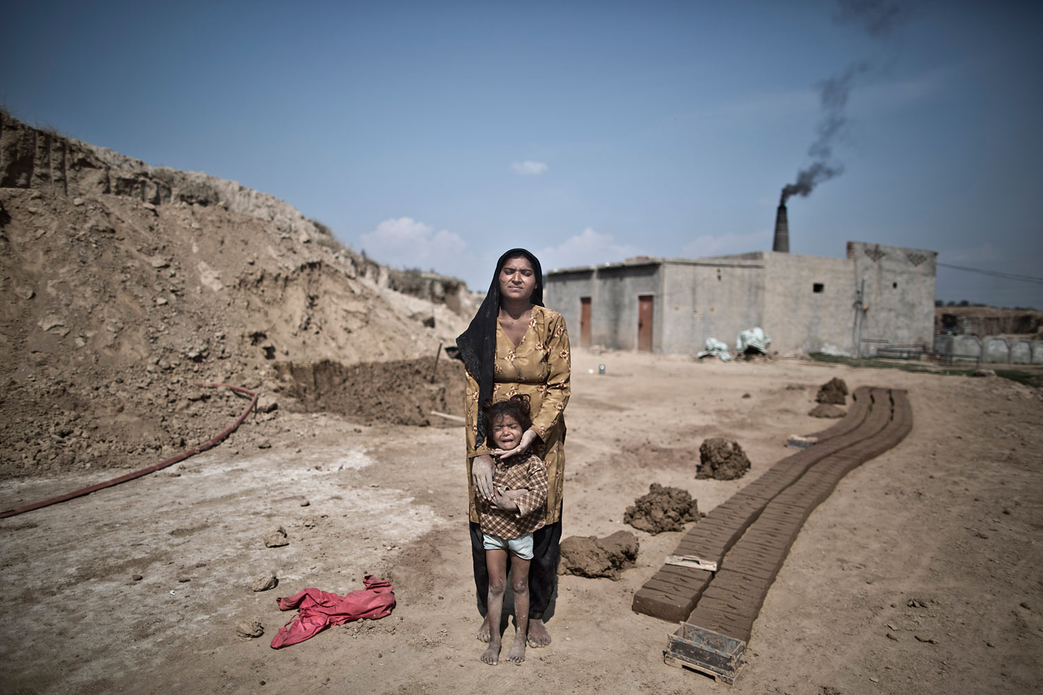 Khurshid Mumtaz, 25, a Pakistani brick factory worker, comforts her crying daughter Haima, 4, while posing for a picture at the site of her work in Mandra, near Rawalpindi, Pakistan, March 2, 2014. Khurshid and her husband are in debt to their employer the amount of 194,000 rupees (approximately $1940).