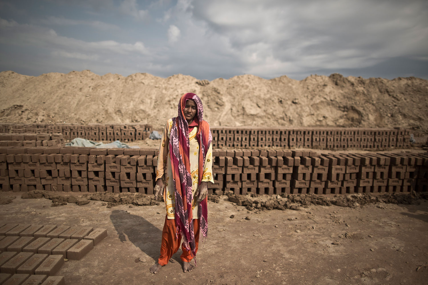 Raina Anwar, 24, a Pakistani brick factory worker, poses for a picture at the site of her work in Mandra, near Rawalpindi, Pakistan, March 5, 2014. Raina and her husband are in debt to their employer the amount of 190,000 rupees (approximately $1900).