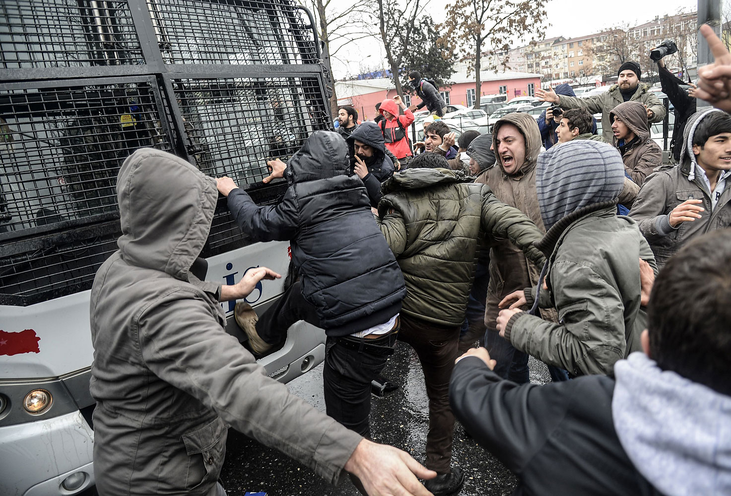 Protesters attack a riot police vehicle during clashes outside Okmeydani Hospital in Istanbul on March 11, 2014.