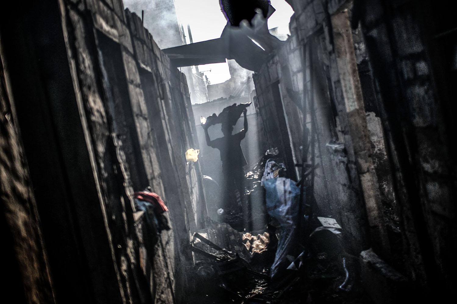 Mar. 23, 2014. A resident collects scrap metal from the rubble of burnt shanties after a fire gutted a residential area in Caloocan city, north of Manila, Philippines.