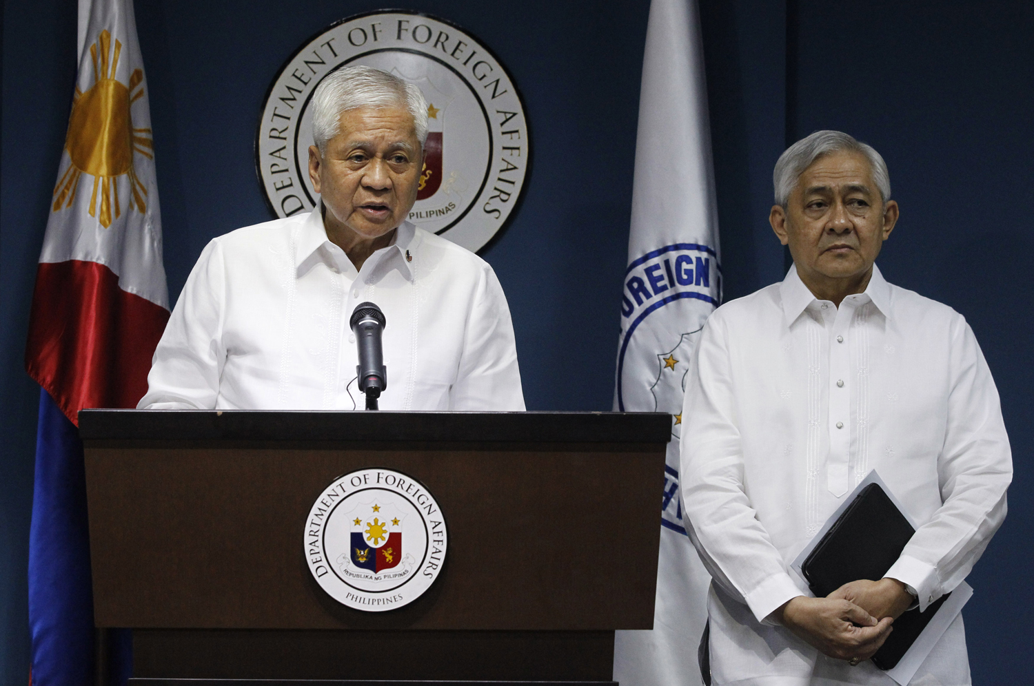 Philippine Foreign Secretary Albert del Rosario (L) stands next to Solicitor General Francis Jardeleza during a news conference in Manila March 30, 2014.