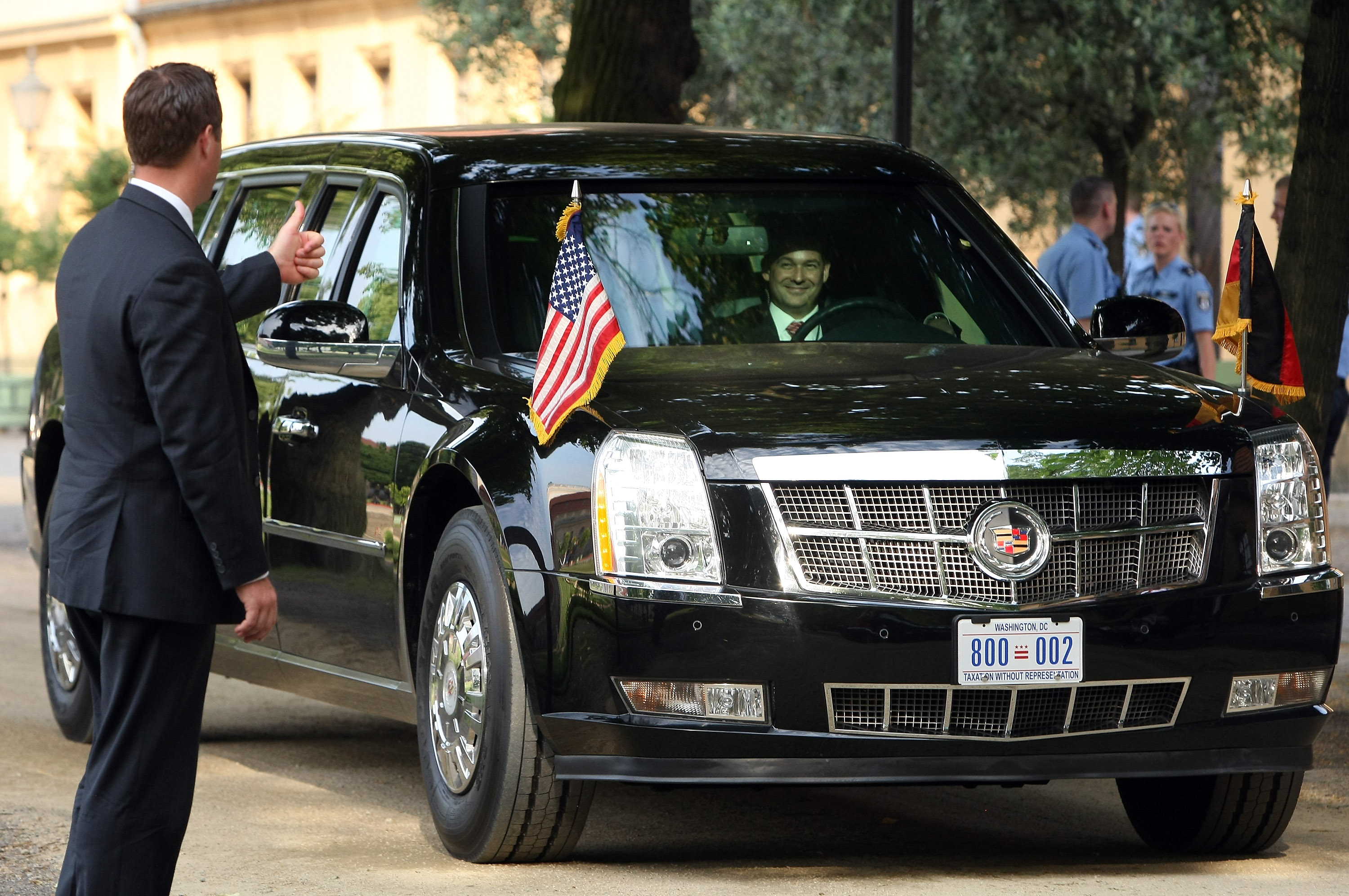 A security officer gives a thumbs-up to the driver of 'The Beast,' a modified Cadillac DTS that is the current U.S. presidential limousine, after U.S. President Barack Obama exited it for a dinner at the Orangerie at Schloss Charlottenburg palace on June 19, 2013 in Berlin.