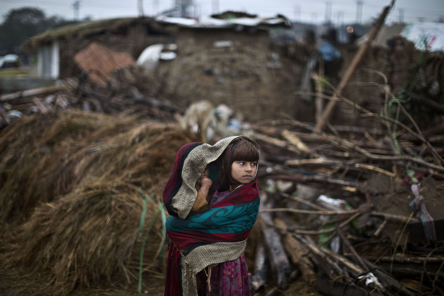 Mar. 24, 2014. An Afghan refugee girl wraps herself and her younger brother with a shawl to shield from the rain.