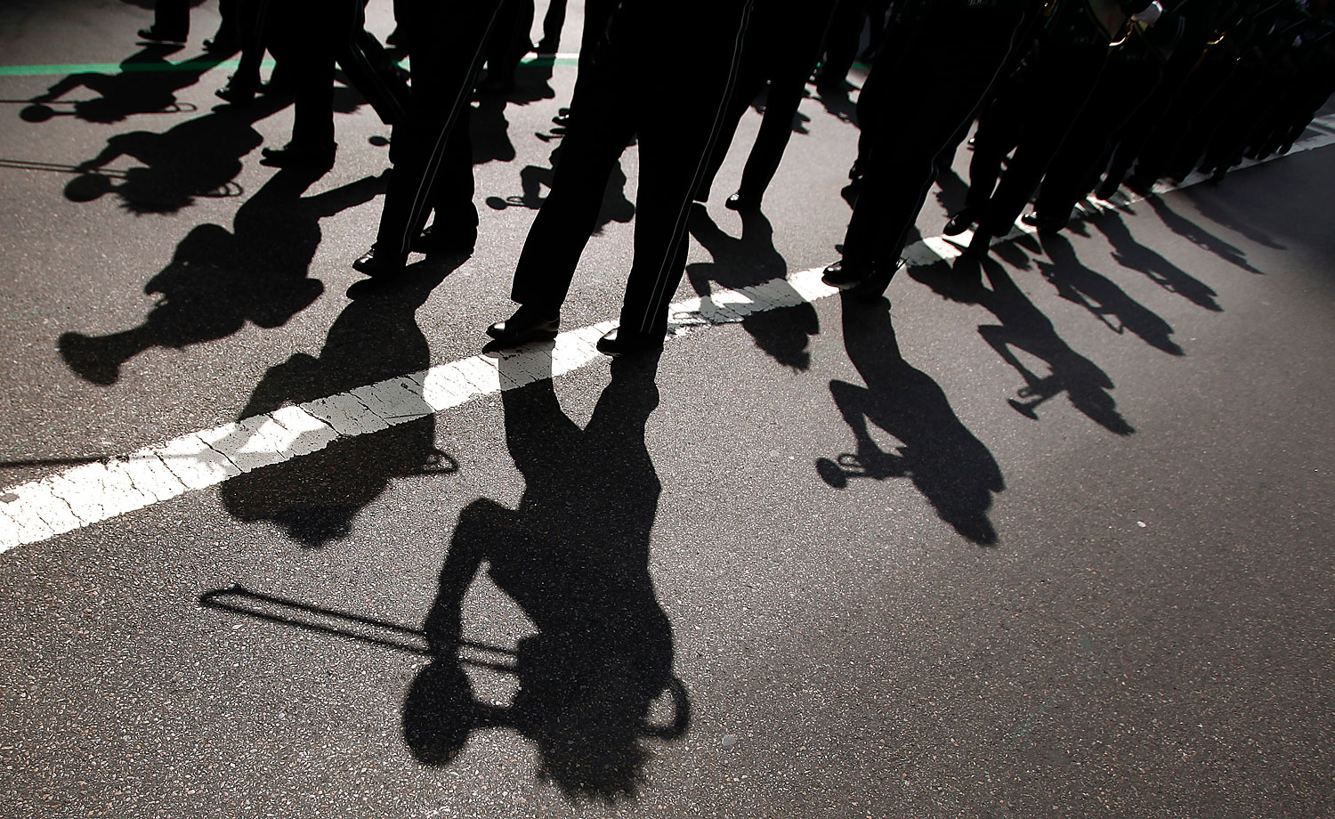 A marching band casts shadows on the road during the 251st annual St. Patrick's Day Parade in New York, March 17, 2012.