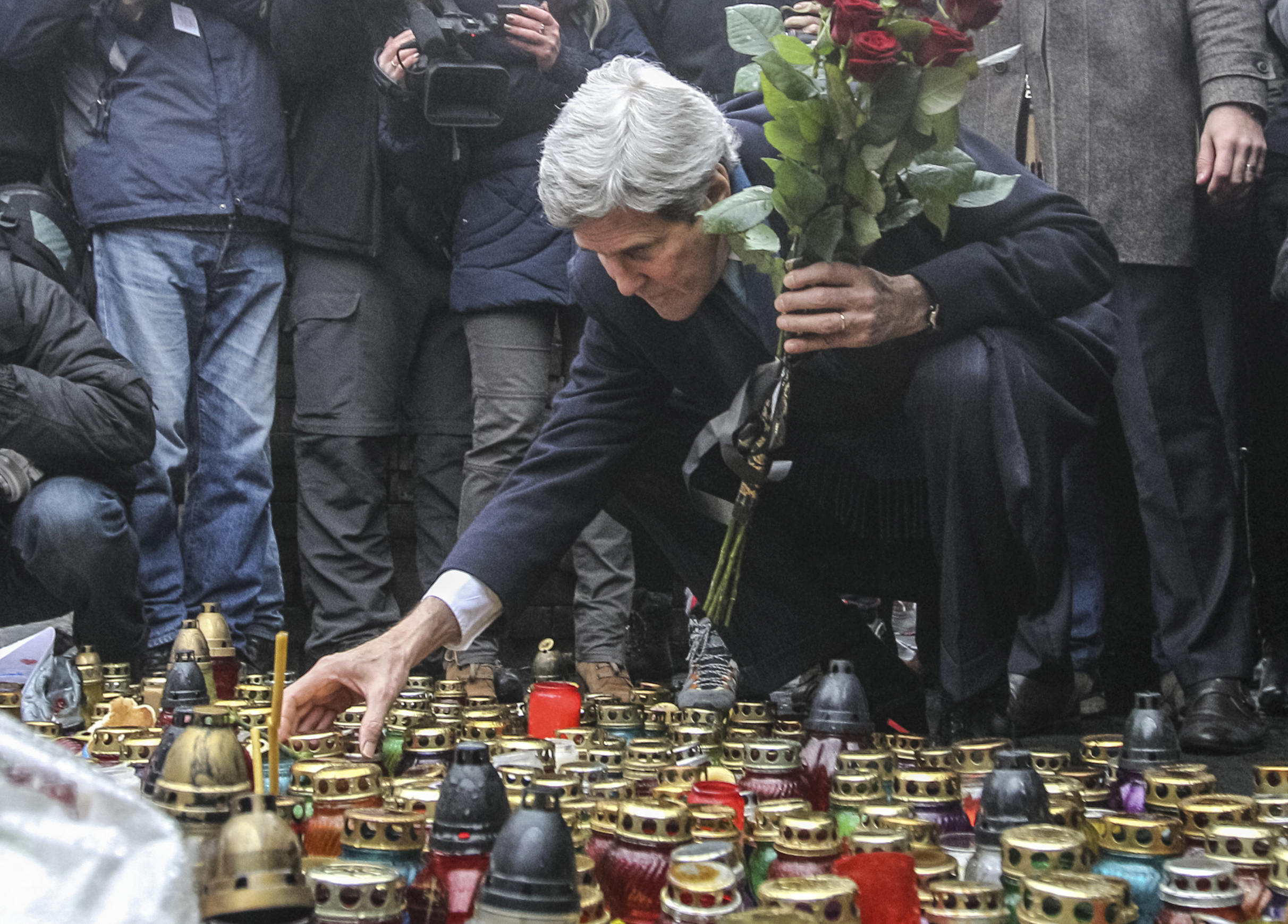 U.S. Secretary of State John Kerry lights a candle and lays roses atop the Shrine of the Fallen in Kiev March 4, 2014.
