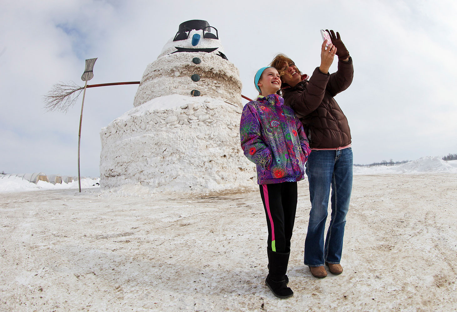 Chris Schueller and  daughter Hope photograph themselves in front of a 50-foot snowman named  Granddaddy  in Gilman, Minnesota, March 6, 2014.
