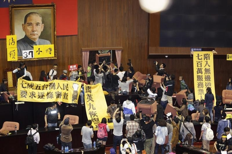 Students and protesters hold banners and chairs inside Taiwan's legislature in Taipei