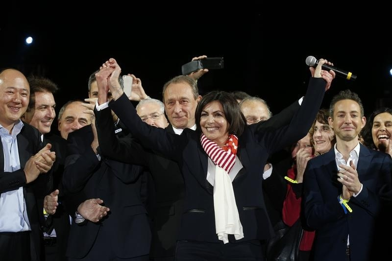 Former Mayor of Paris Bertrand Delanoe and his newly-elected successor Anne Hidalgo celebrate her victory at City Hall Plaza on March 30, 2014 in Paris.