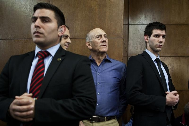 Former Israeli Prime Minister Ehud Olmert (center) waits to hear his verdict at the Tel Aviv District Court on March 31, 2014.