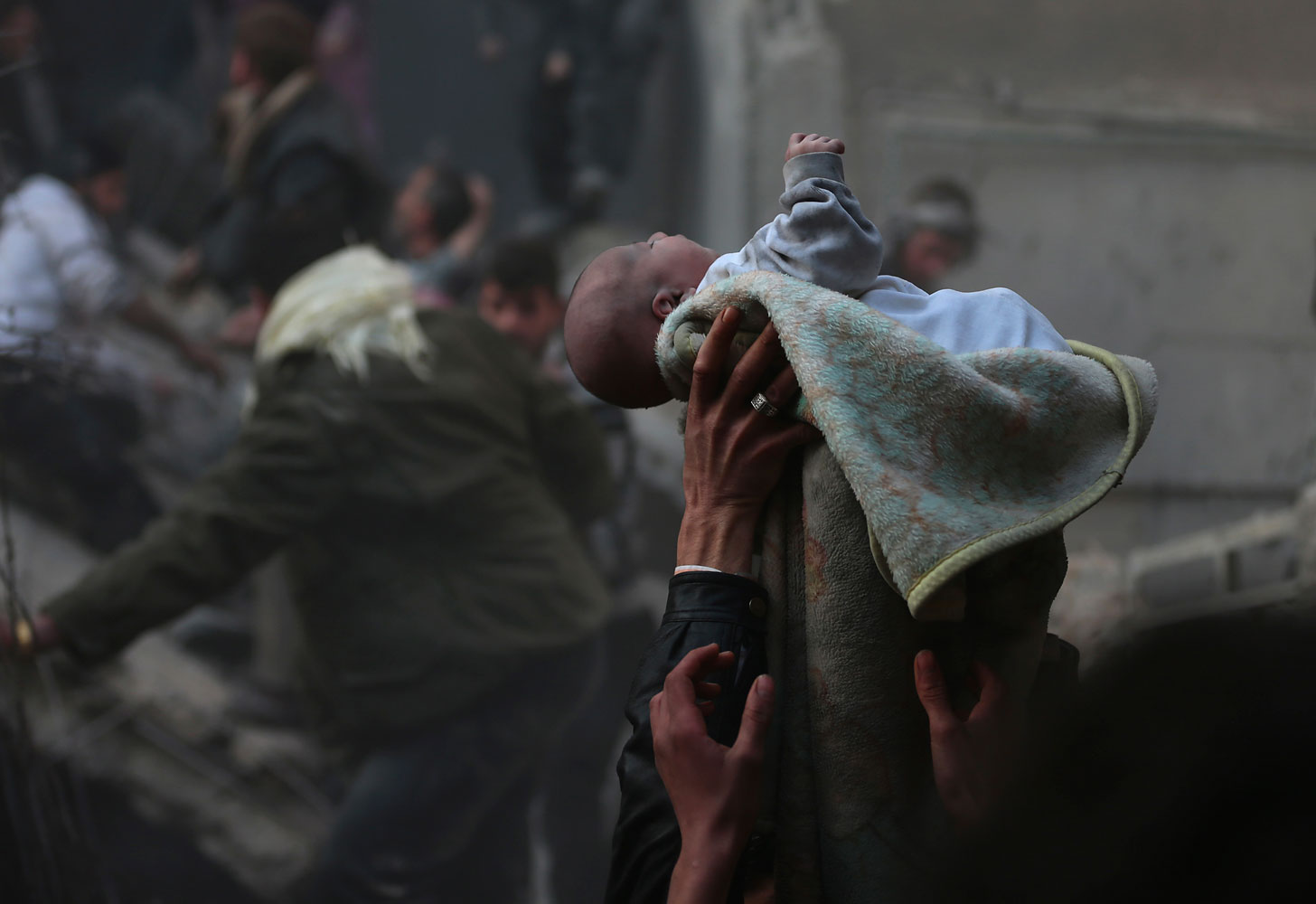 Men hold up a baby saved from under rubble, who survived what activists say was an airstrike by forces loyal to Syrian President Bashar al-Assad in the Duma neighbourhood of Damascus, Jan. 7, 2014.