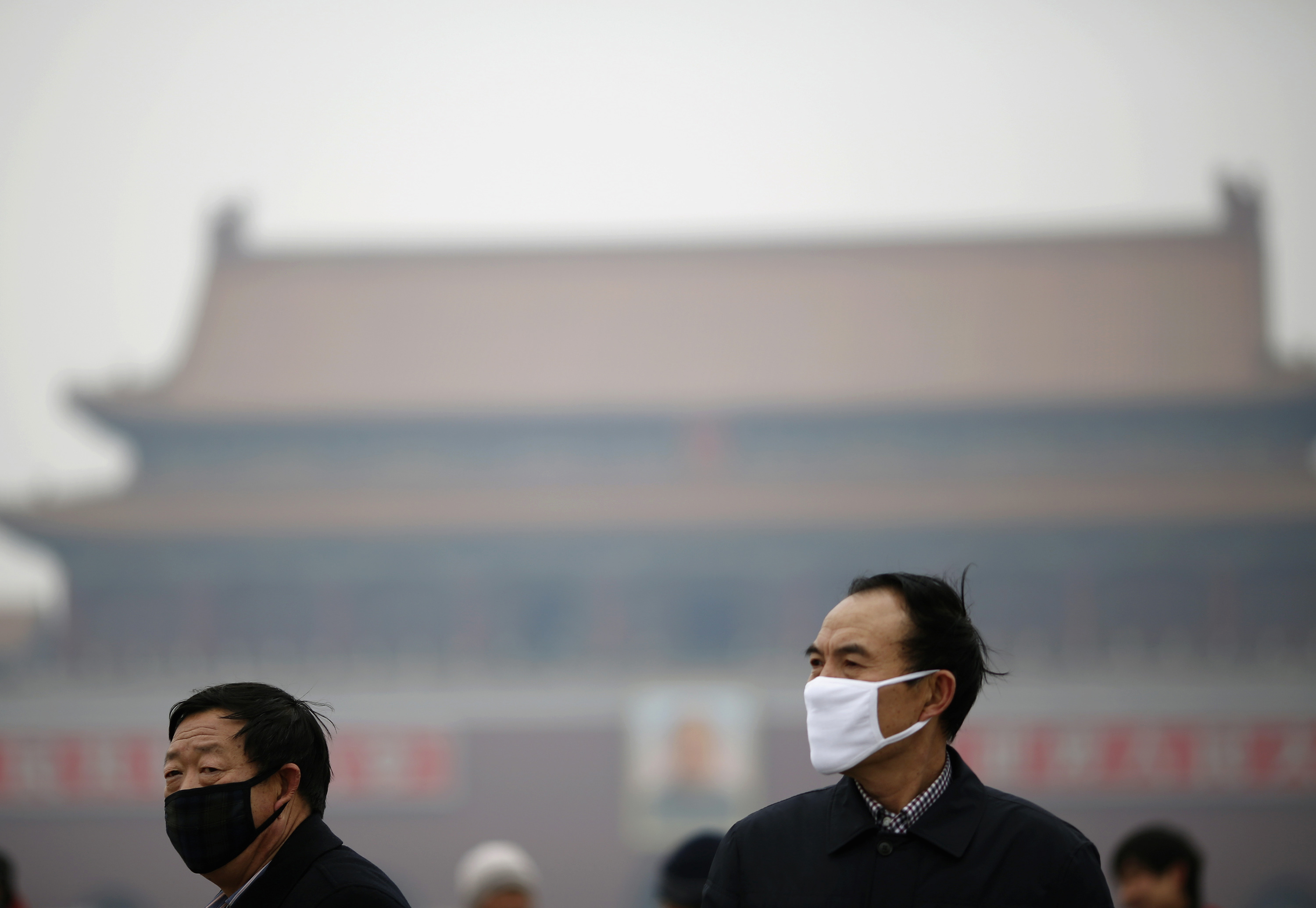 People wearing masks are seen on a hazy day at Tiananmen Square in Beijing February 13, 2014.