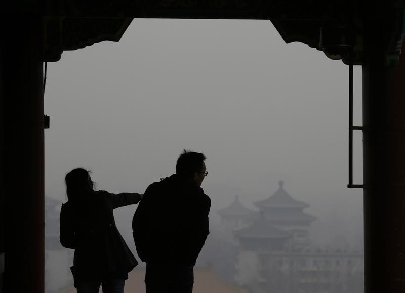 Visitors are silhouetted against thick smog on the top of Jingshan Park near the Forbidden City in Beijing