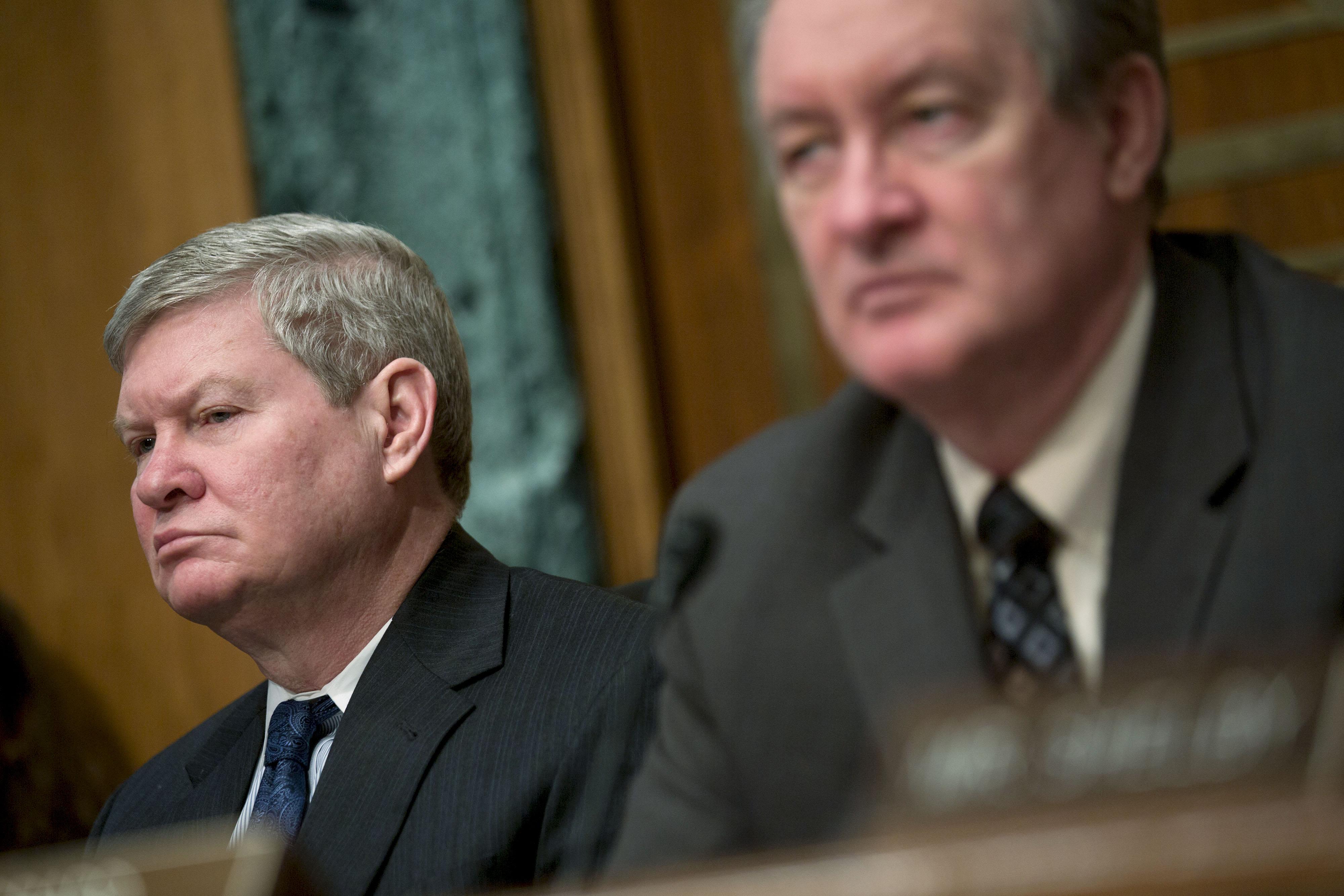Senator Tim Johnson, chairman of the Senate Banking Committee, left, and Senator Mike Crapo listen during a Senate Banking Committee hearing in Washington, Feb. 27, 2014.