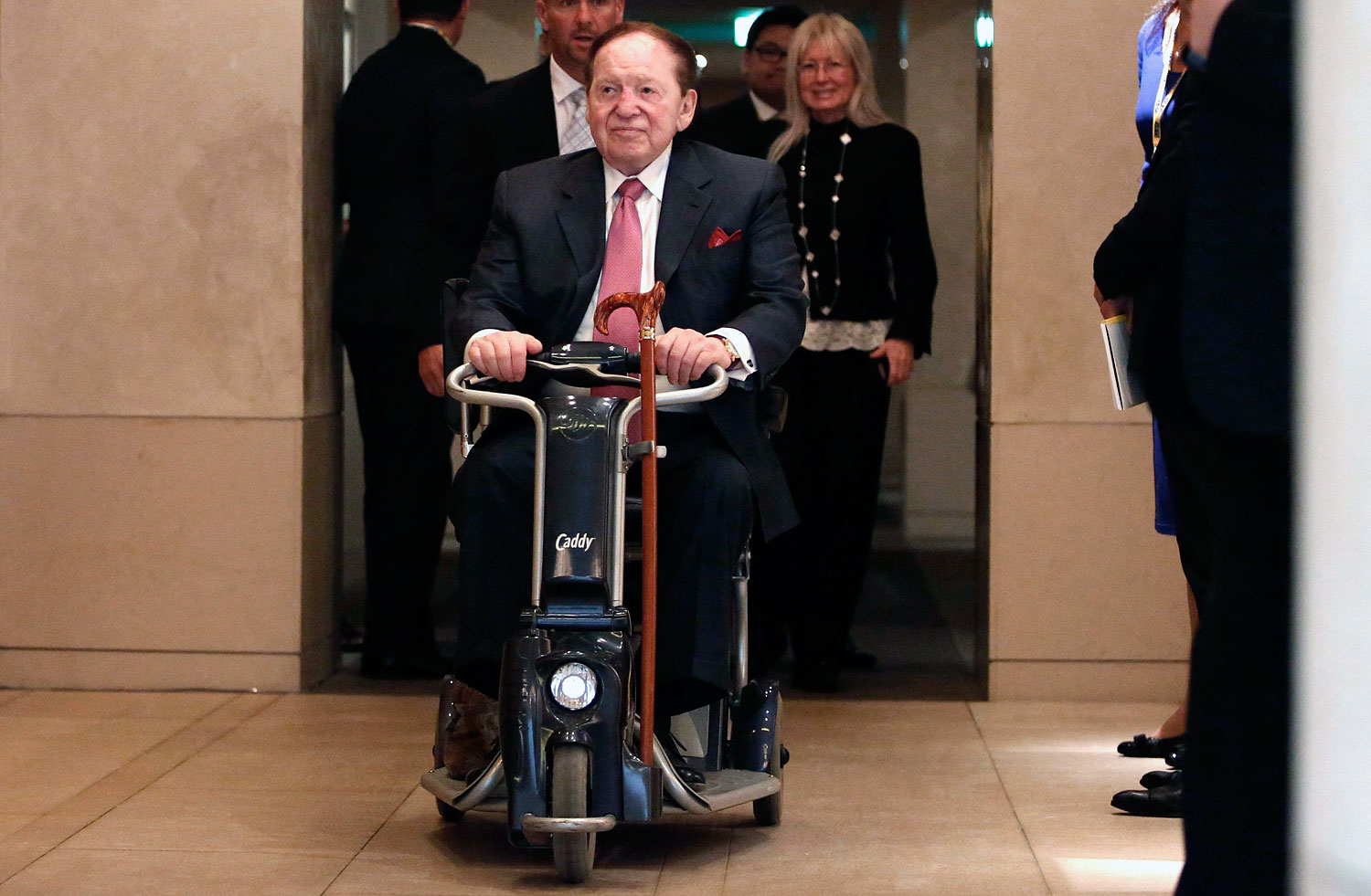Las Vegas Sands Corp Chairman and Chief Executive Officer Sheldon Adelson rides his wheelchair after a news conference in Tokyo , Feb. 24, 2014