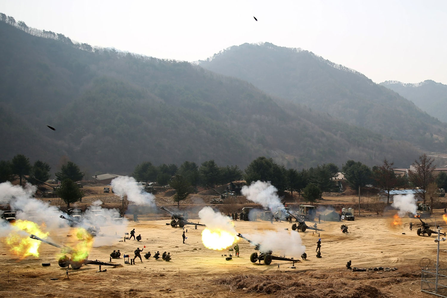 Mar. 27, 2014. Towed 155mm Howitzers fire during an artillery drill in Inje, near the demilitarized zone (DMZ) which separates the two Koreas in this picture provided by South Korean Army and released by Yonhap.