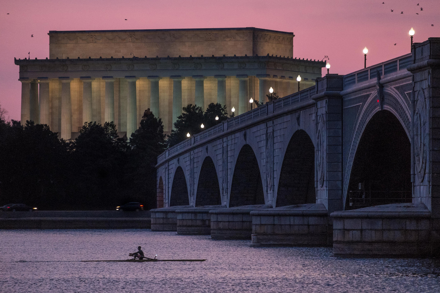 Mar. 21, 2014. A solitary rower skims across the Potomac River past the Lincoln Memorial and under the Memorial Bridge at sunrise in Washington DC.