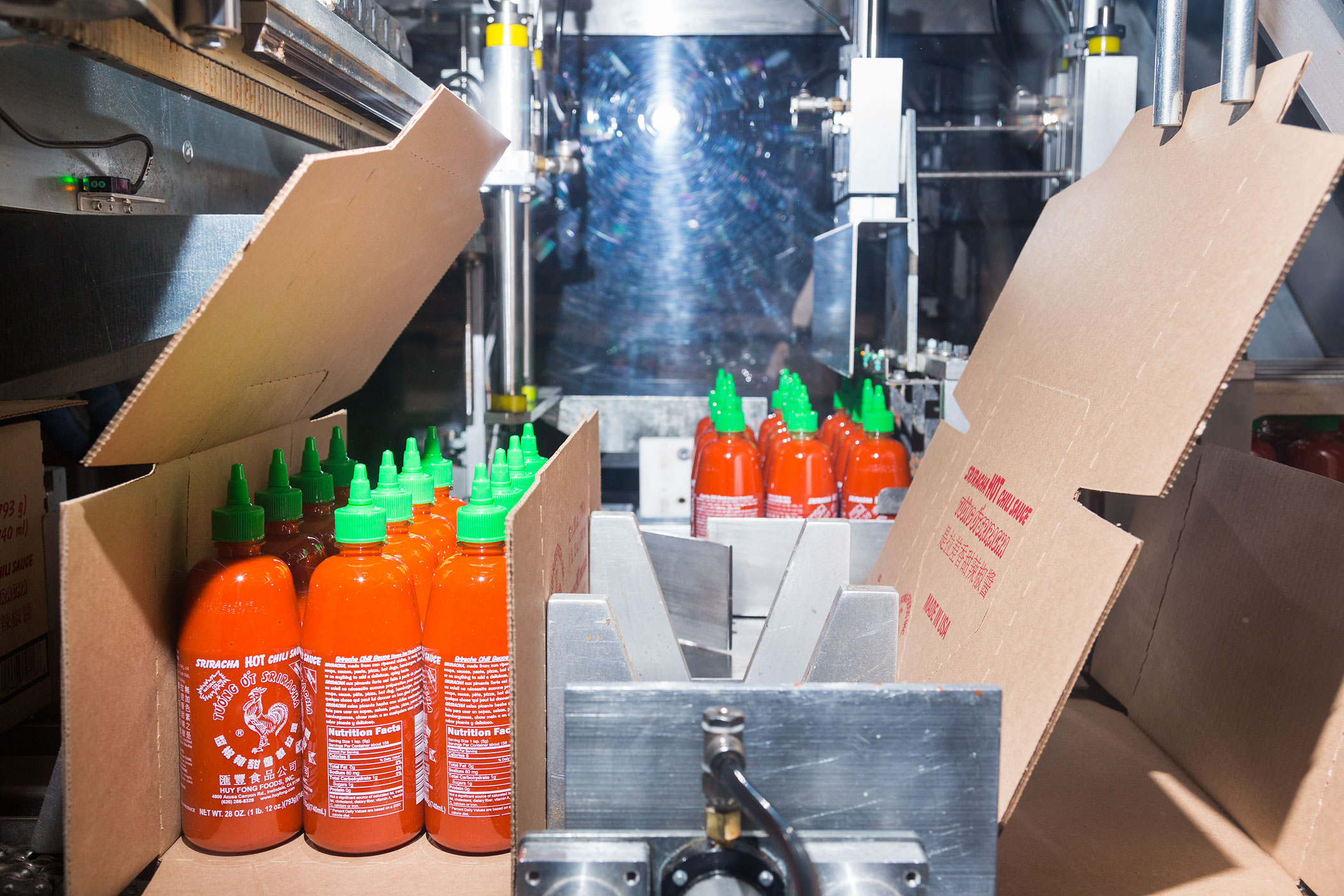 A machine boxes Sriracha bottles that will end up in restaurants and on grocery store shelves.