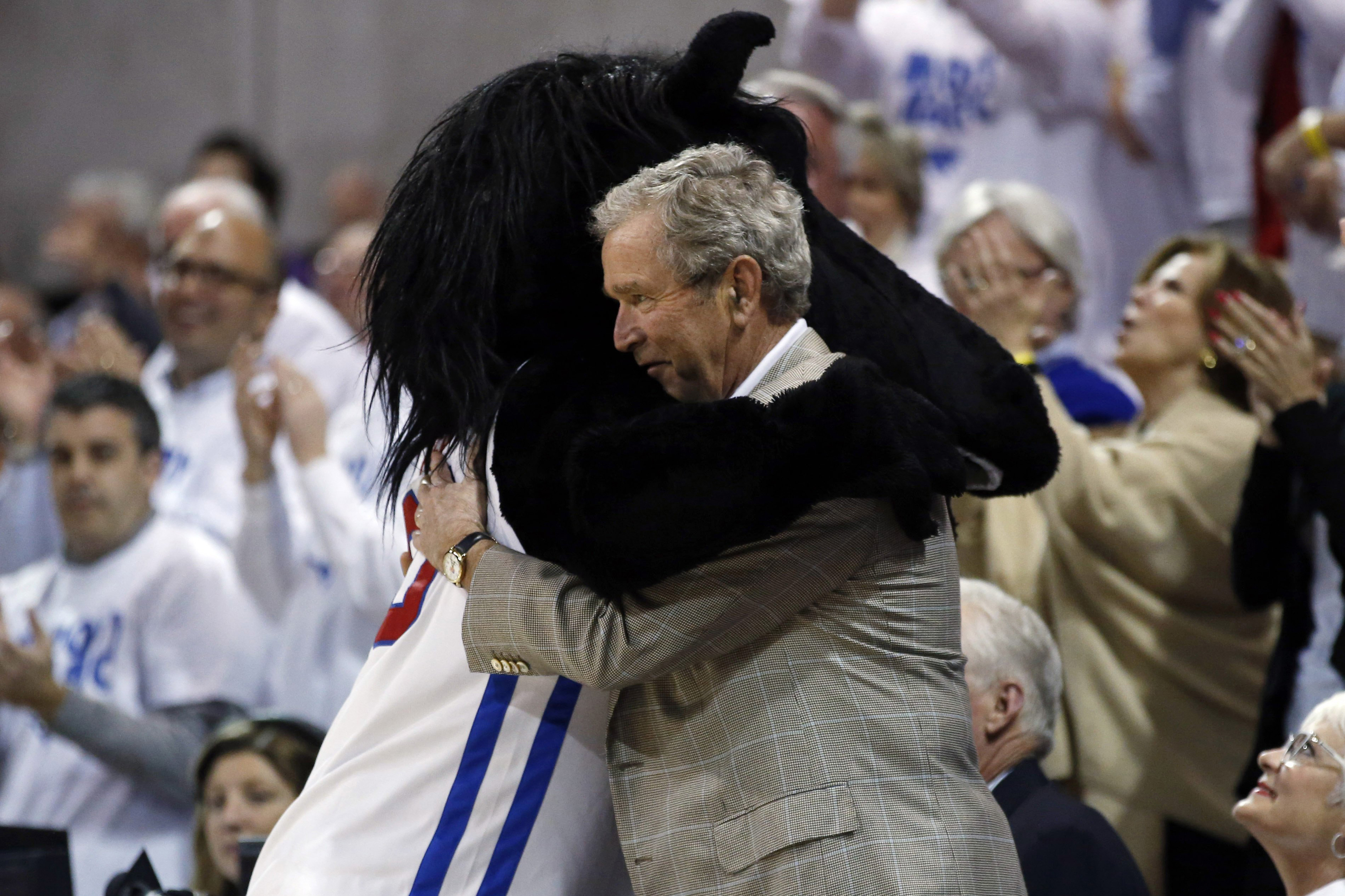 Former President George W. Bush gets a hug from SMU mascot Peruna during a break in the first of an NCAA college basketball game between SMU and Louisville on March 5, 2014, in Dallas.