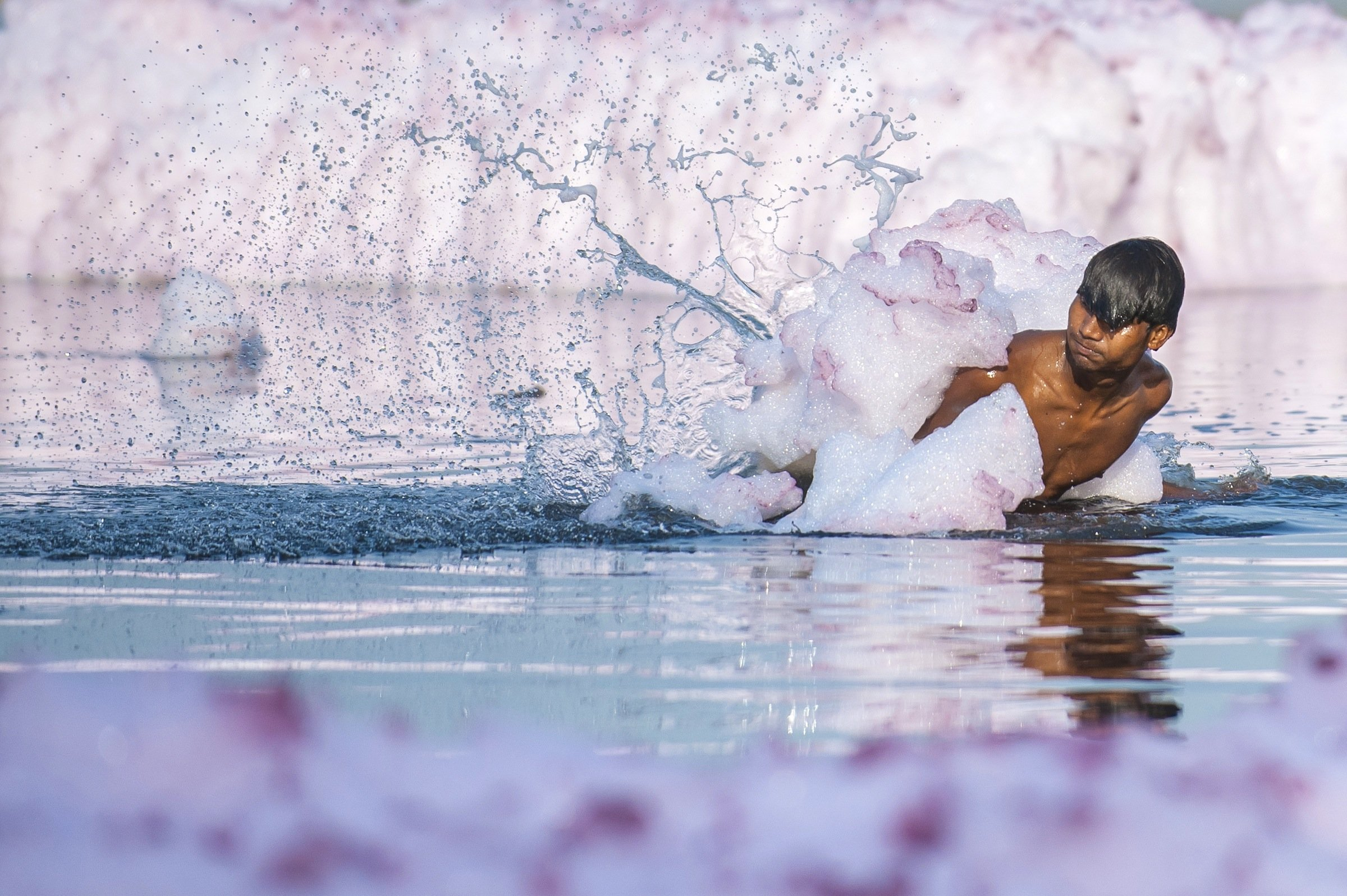 A man tries to get rid of a thick layer of flowing foam, caused by extreme pollution, as he takes a bath in river Yamuna on March 19, 2014 in New Delhi. Yamuna is the largest tributary of the holy river, Ganges, and has often been described as the most polluted water body in northern India.
