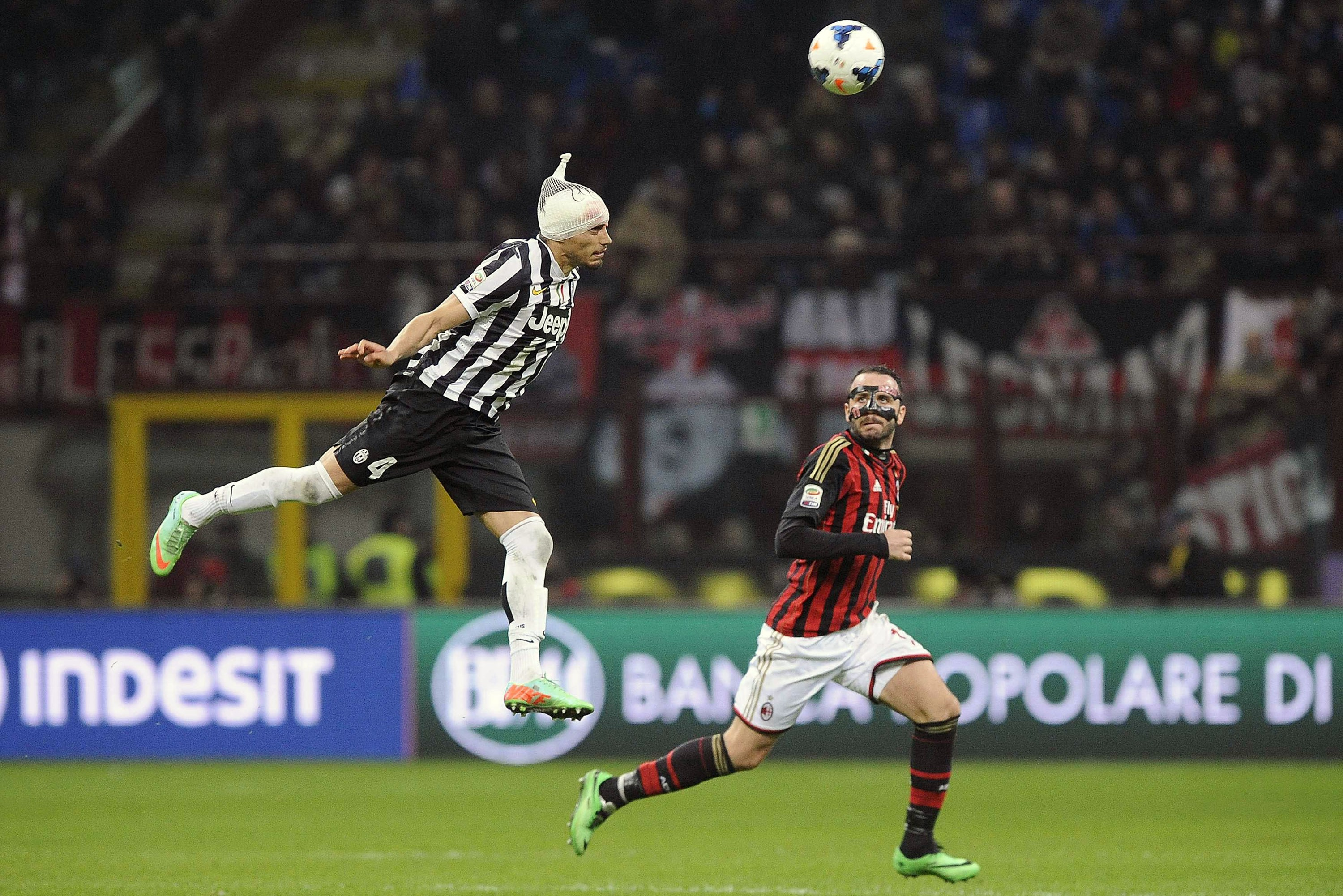 Juventus' Martin Caceres, left, jumps for the ball as AC Milan's Giampaolo Pazzini looks at him during their Italian Serie A soccer match at the San Siro stadium in Milan March 2, 2014.