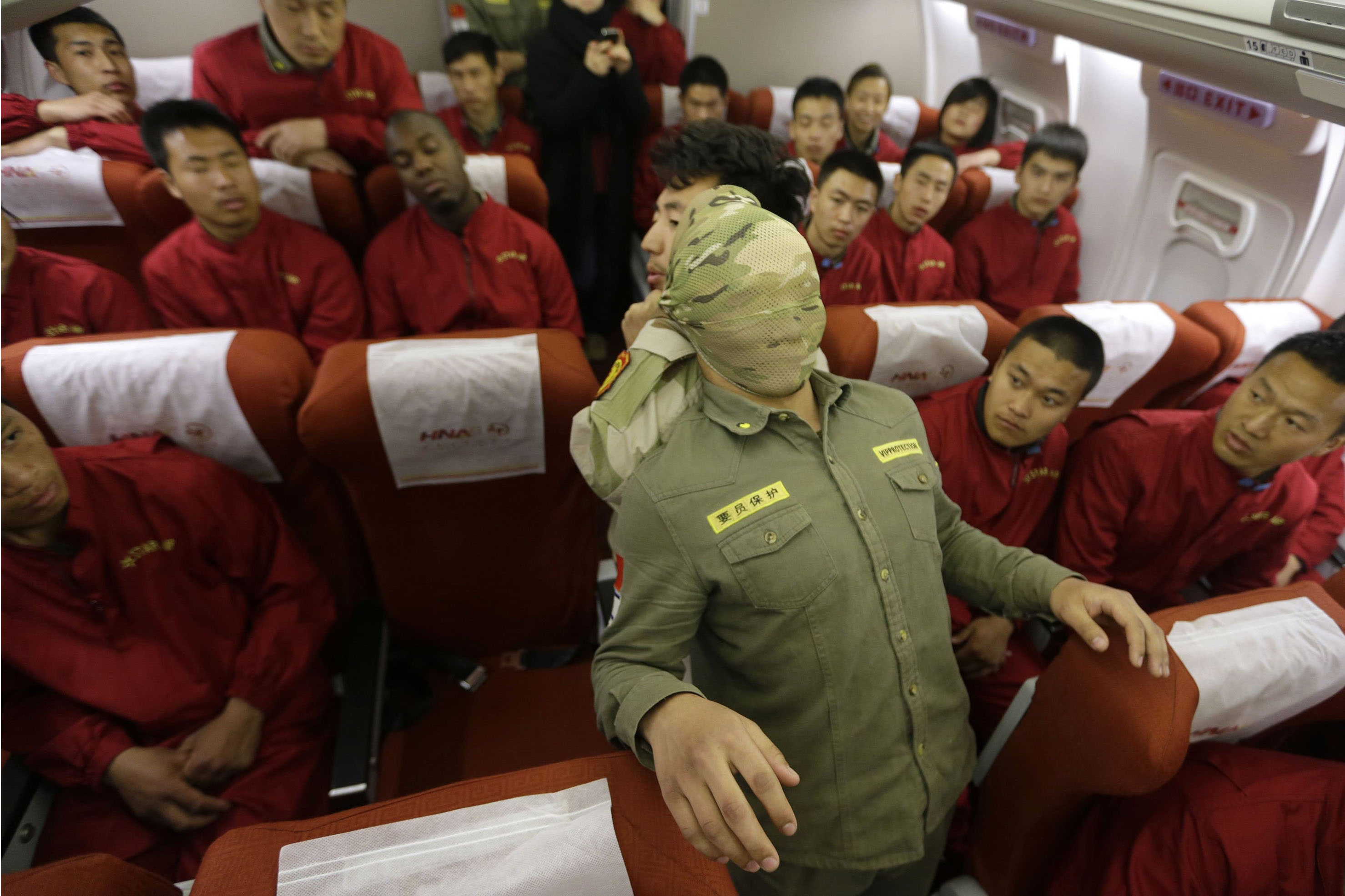 Trainees of the Tianjiao Special Guard/Security Consultant bodyguard training camp watch their instructor use a scarf to cover a student's head during a demonstration of close-quarter combat skills at a special course on flight safety inside a scale model of a passenger jet at a flight attendant training centre on the outskirts of Beijing, March 18, 2014. Inspired by the missing Malaysia Airlines Flight MH370, the company wanted to emphasize the importance of aviation safety by teaching their trainees emergency evacuation procedures and close-quarter combat skills to handle situations such as natural disasters and plane hijacks, according to the company. REUTERS/Jason Lee (CHINA - Tags: SOCIETY TRANSPORT)