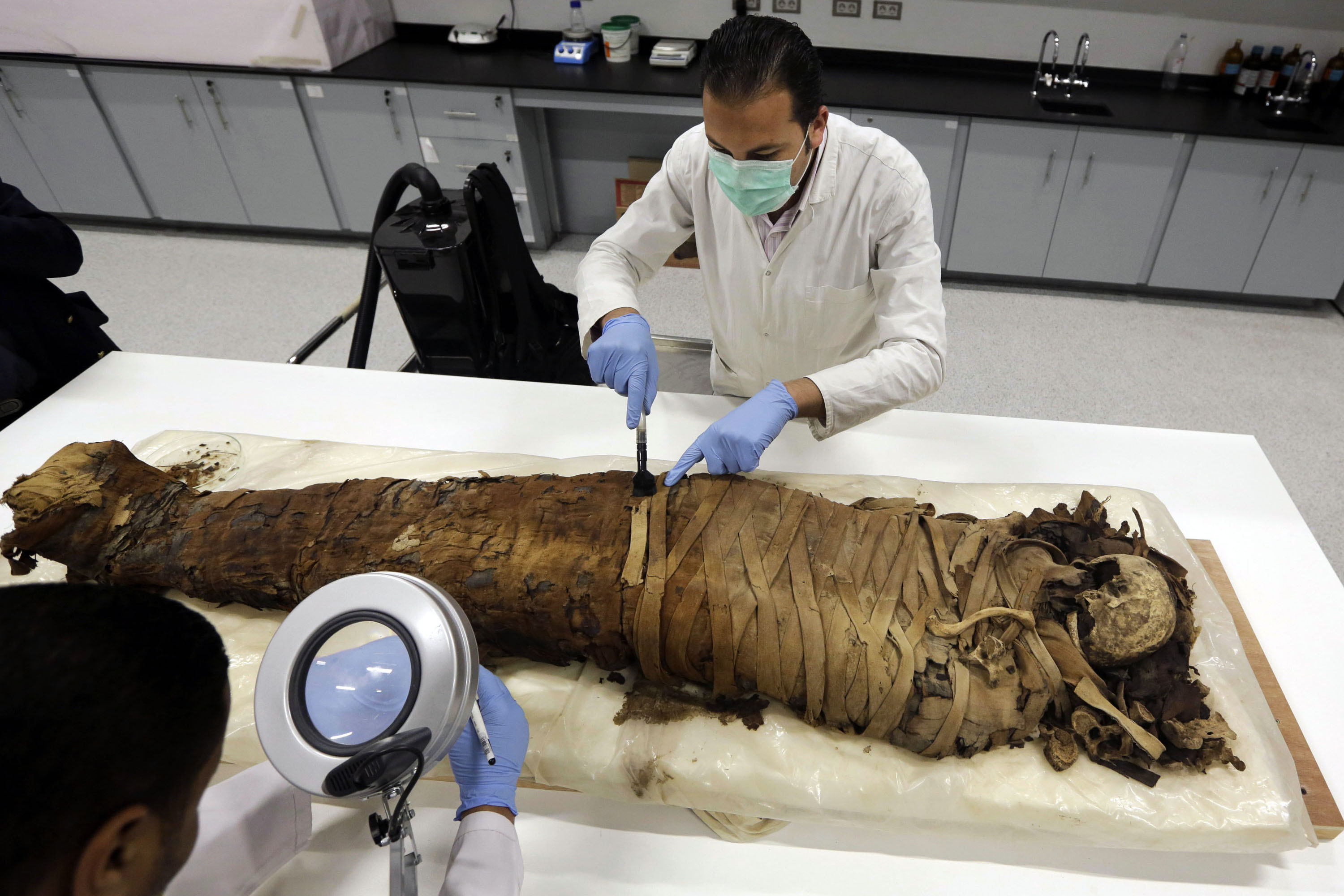 Egyptian conservators clean a female mummy dated to Pharaonic late period, (712-323 BC), in the conservation center of Egypt's Grand museum under construction, just outside Cairo, Egypt, Monday, March 17, 2014. Egyptís antiquities minister says construction has begun on the main hall of a massive new museum by the Pyramids, the final phase of a complex thatís intended to house 100,000 ancient artifacts including King Tutankhamun's mummy. (AP Photo/Amr Nabil)