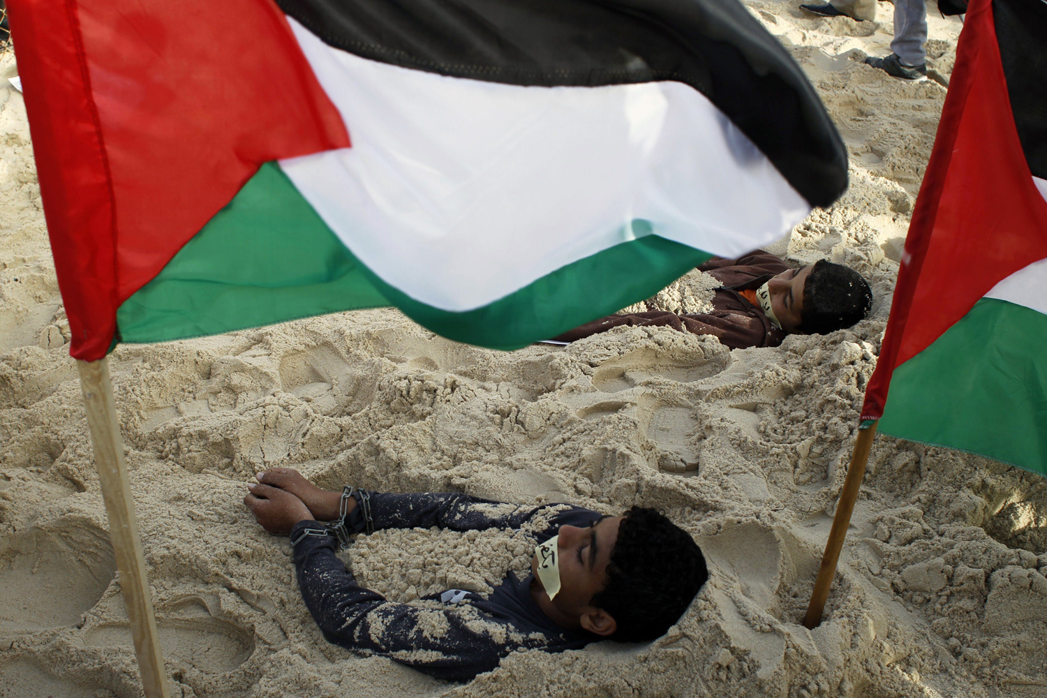 Palestinian children lie in the sand with their hands clasped next to their national flags during a rally against the siege on the impoverished Hamas-run Gaza Strip in the coastal town of Rafah on March 7, 2014.