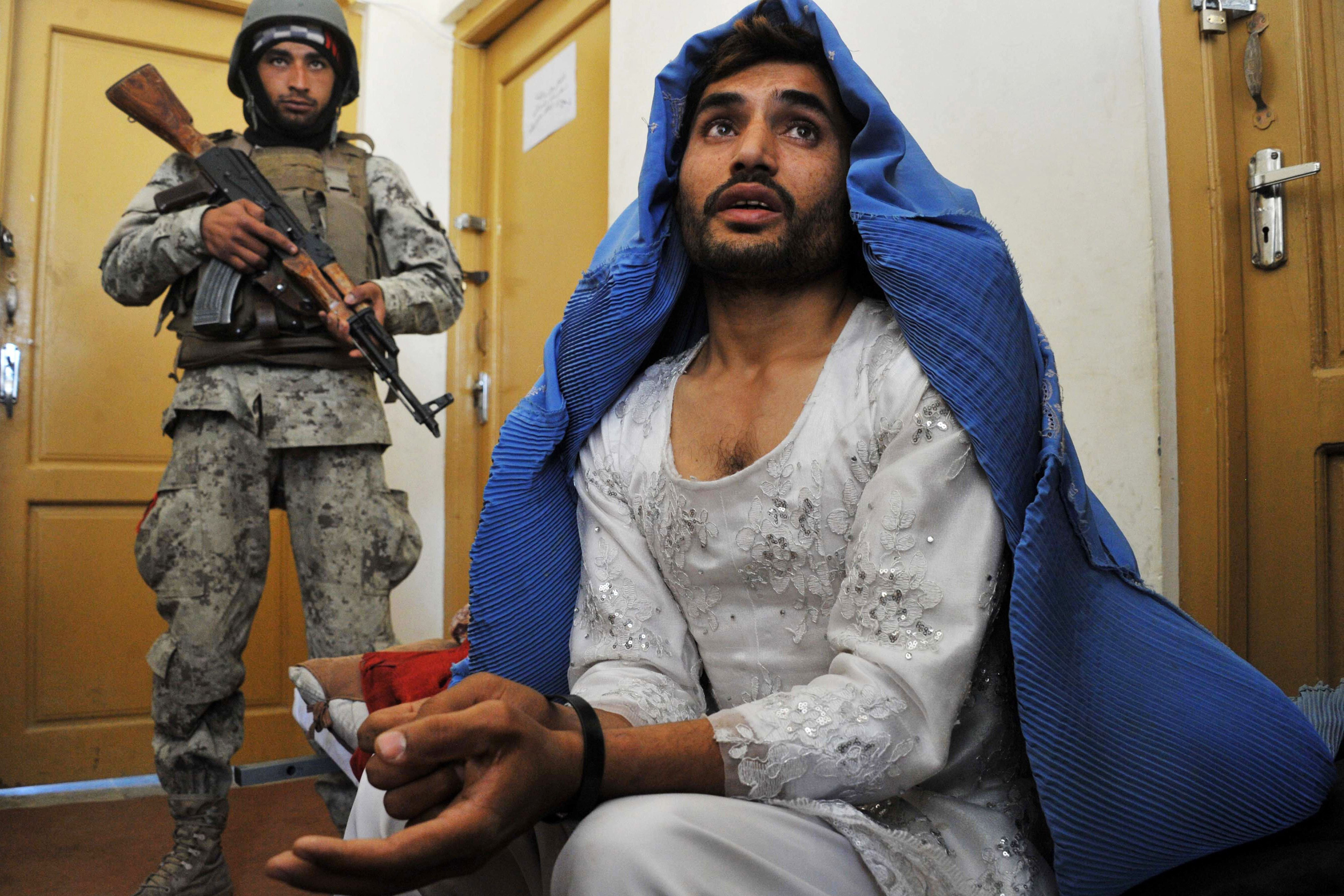 TOPSHOTS                               Afghan security personnel present a burqa-clad resident they say is a Taliban fighter to the media at the Afghan National Army headquarters in Khogyani District near Jalalabad on March 18,2014. Three Taliban insurgents have been arrested in possession of heroin by Afghan Joint Forces during an operation in the Khogyani District of Nangarhar province.  AFP PHOTO / Noorullah ShirzadaNoorullah Shirzada/AFP/Getty Images