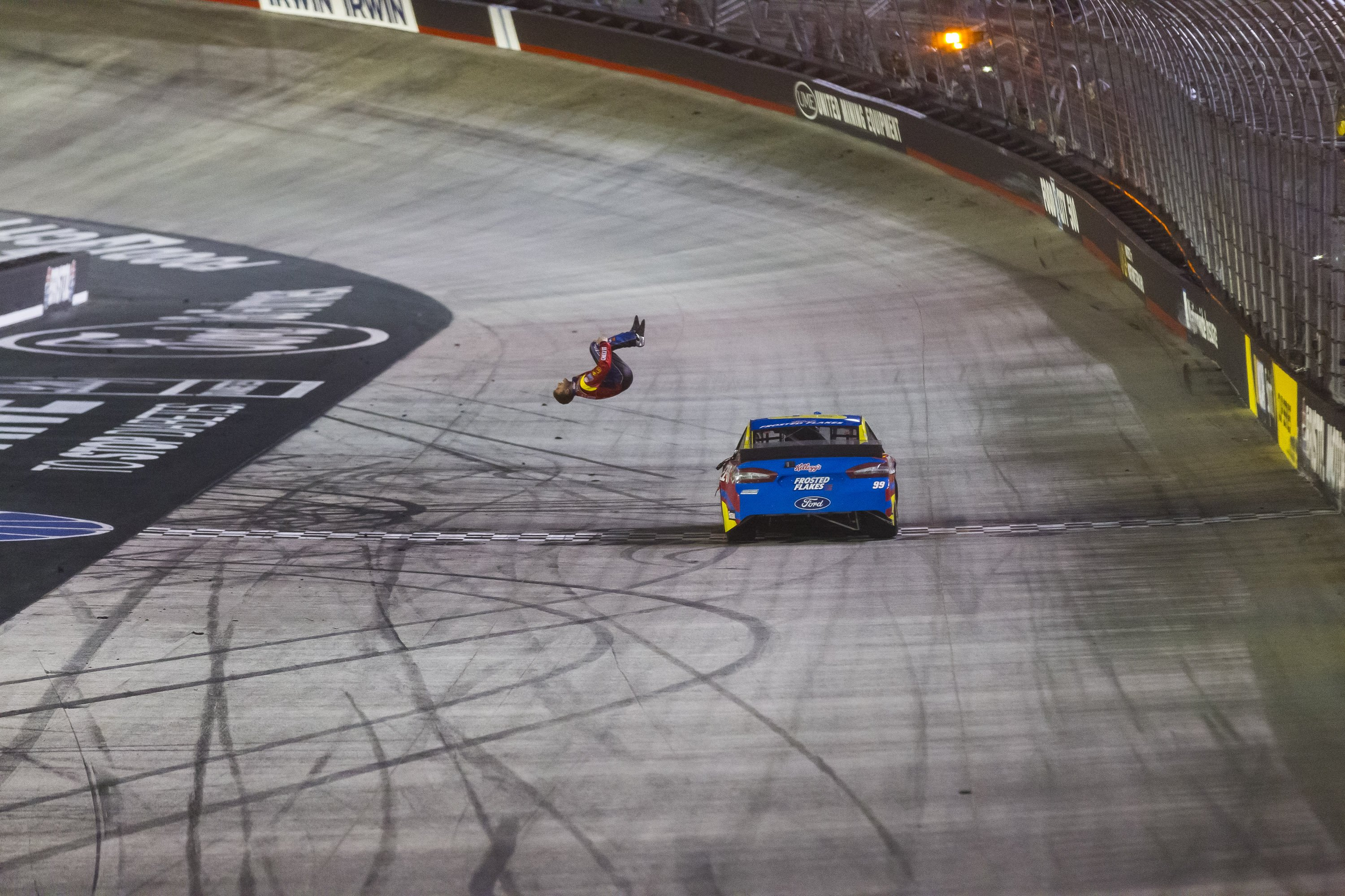 Driver Carl Edwards does a back flip off of the Roush Fenway Racing #99 Ford Fusion after winning the Sprint Cup series Food City 500 at Bristol Motor Speedway in Bristol, Tenn.