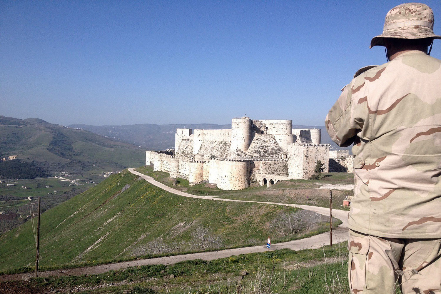 A government soldier looks out over the renowned Crusader castle Krak des Chevaliers near the Syria-Lebanon border after forces loyal to Syria's President Bashar al-Assad seized the fortress on March 20, 2014.