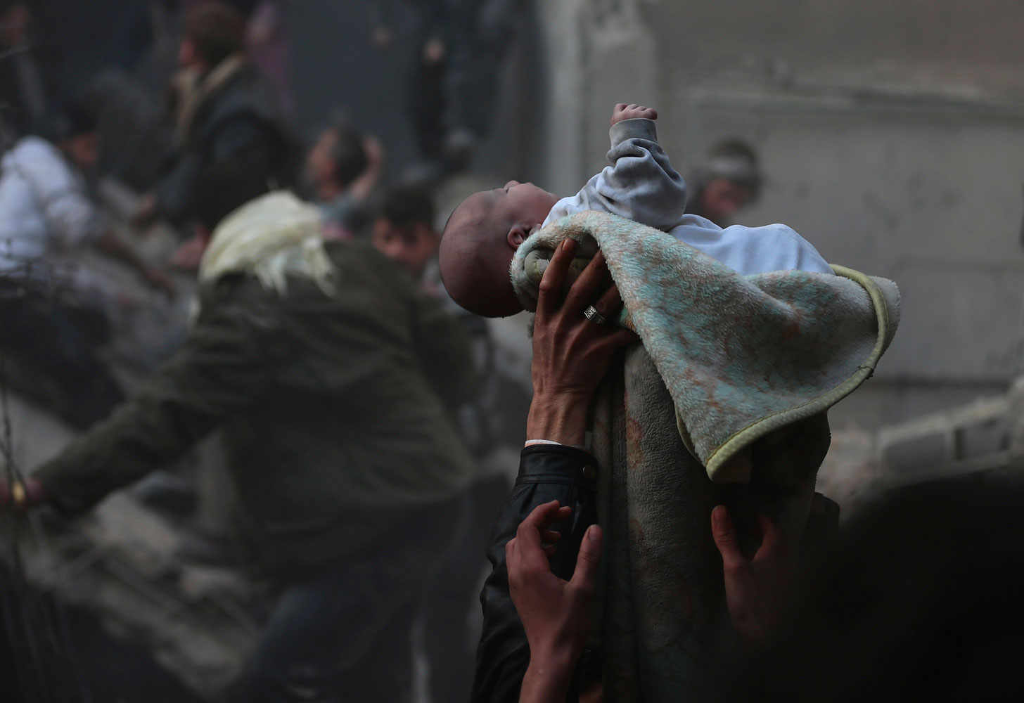 Men hold up a baby saved from what activists say was an airstrike by forces loyal to Syrian President Bashar al-Assad in Damascus on  January 7, 2014.