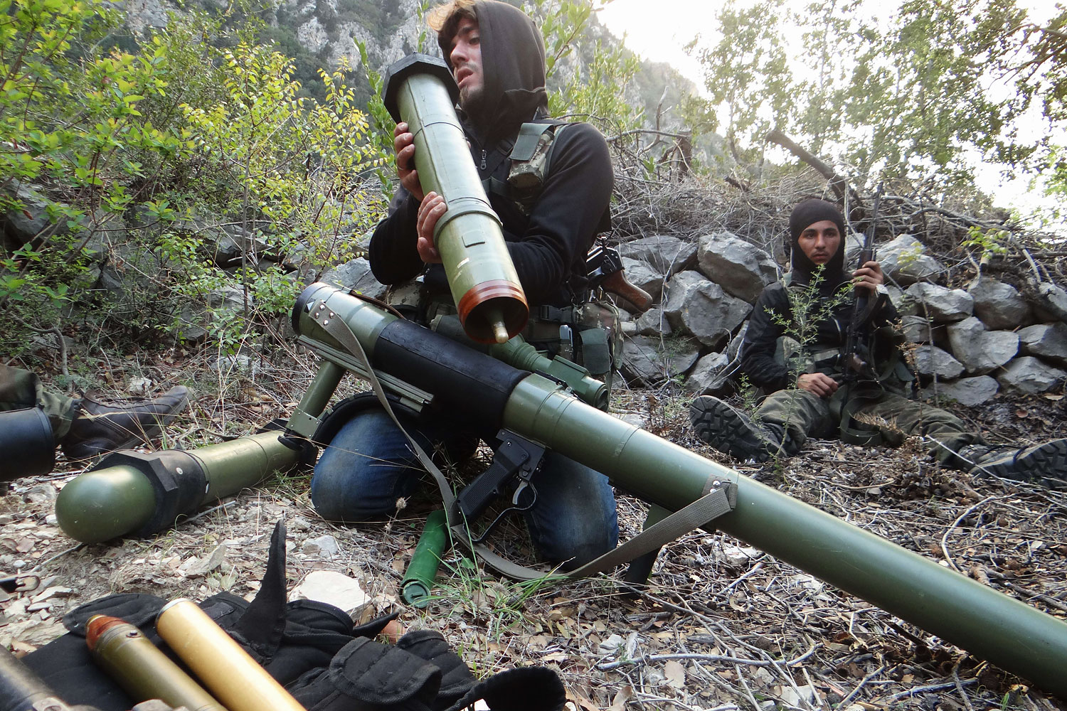 A rebel fighter checks a launcher near the village of Kessab and the border crossing with Turkey, in the northwestern province of Latakia, on March 23, 2014.  Rebels seized Kessab a day later.